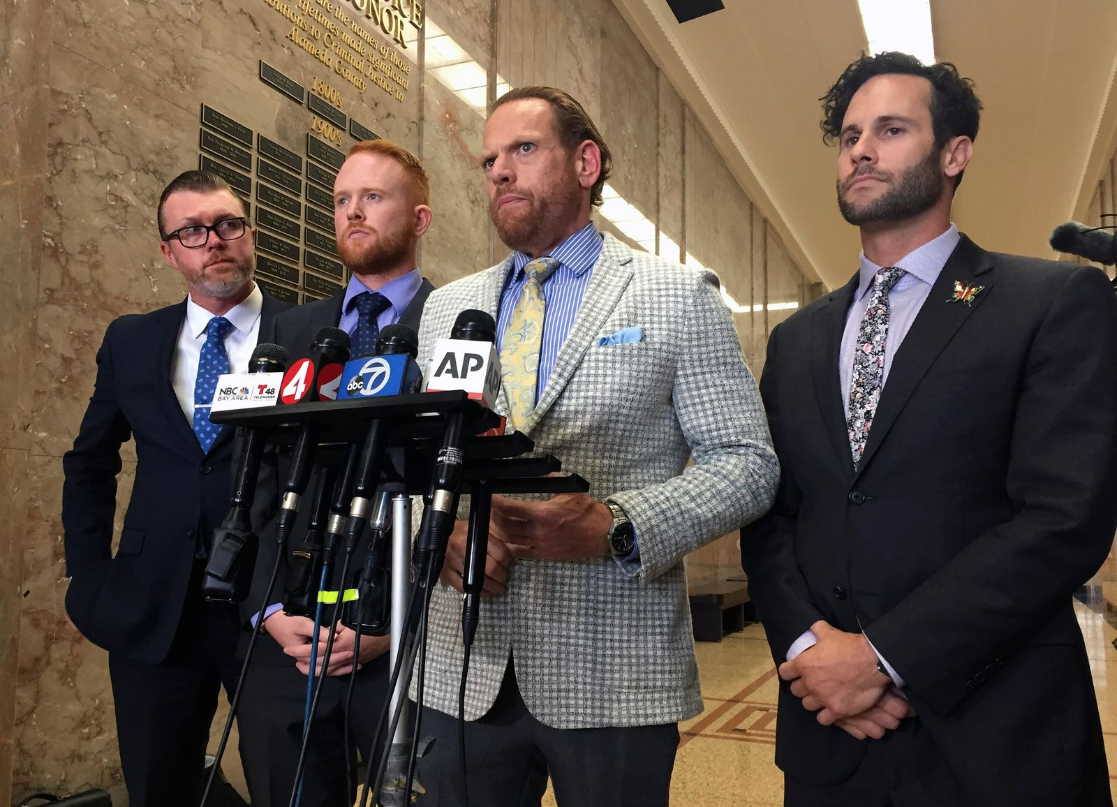 Curtis Briggs, second from right, the attorney for Max Harris, speaks at the courthouse in Oakland, Calif., Thursday, Sept. 5, 2019. A jury has acquitted Max Harris of involuntary manslaughter but couldn't reach a verdict for the leader of an artists' commune accused of turning a California warehouse into a cluttered maze that trapped 36 partygoers during a fast-moving fire. (AP Photo/D. Ross Cameron)