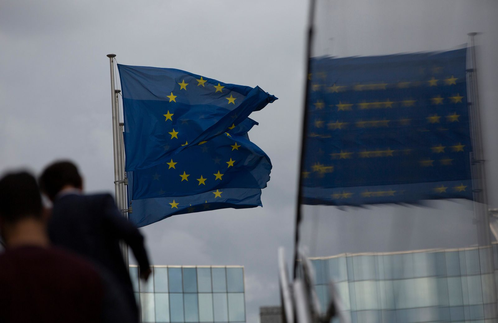 European Union flags flap in the wind as two people walk up a set of stairs outside EU headquarters in Brussels, Sunday, Oct. 13, 2019. (AP Photo/Virginia Mayo)