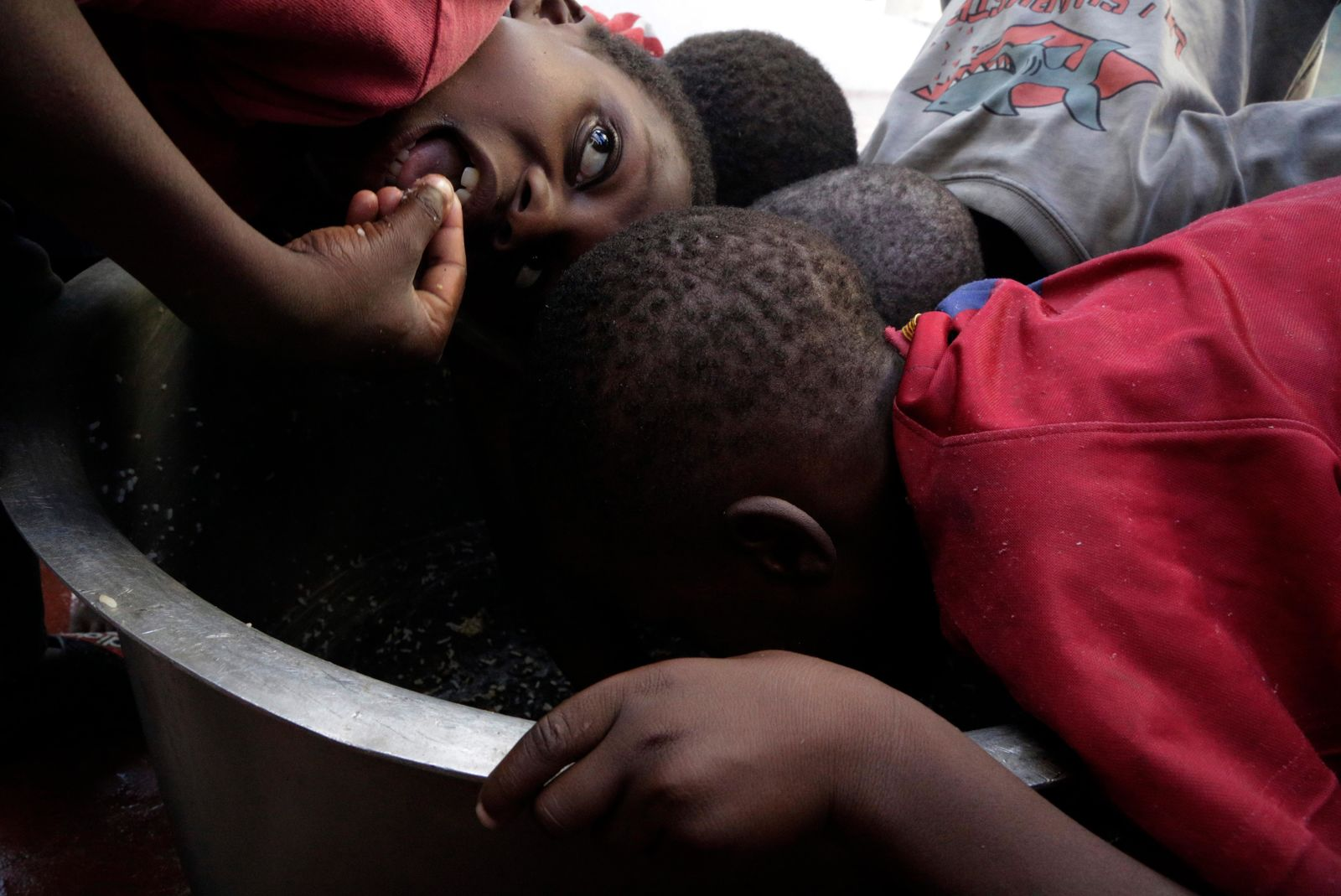 Kids scrape through for remaining rice inside a pot at a displacement centre in Beira, Mozambique, Friday, March 22, 2019.(AP Photo/Themba Hadebe)