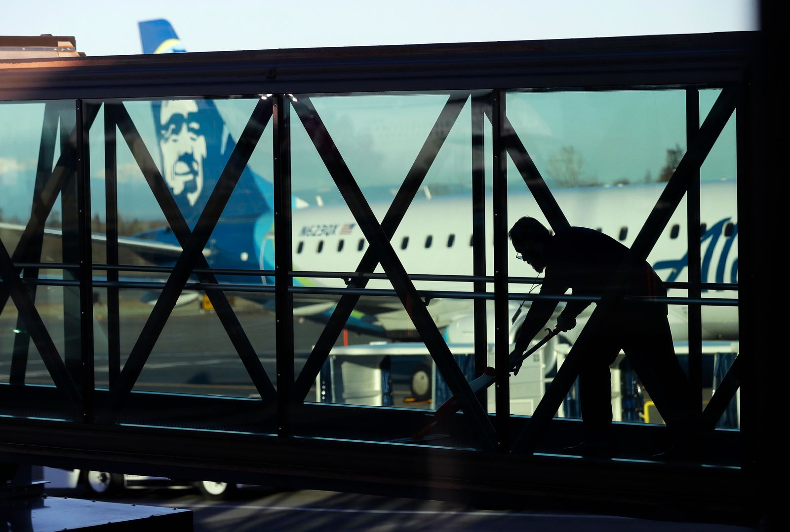 FILE- In this March 4, 2019, file photo a worker cleans a jet bridge before passengers boarded an Alaska Airlines flight to Portland, Ore., at Paine Field in Everett, Wash. (AP Photo/Ted S. Warren, File)