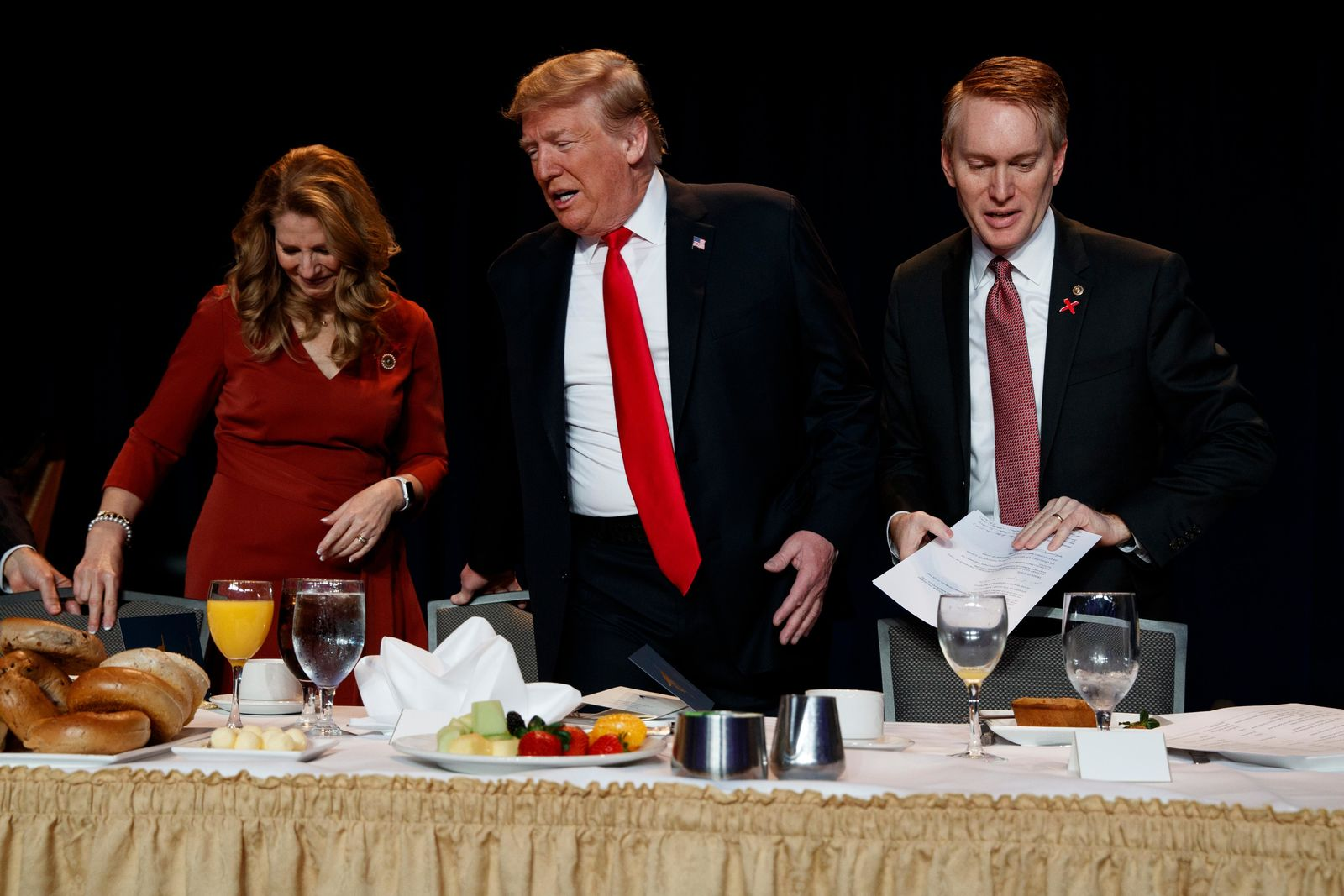 President Donald Trump, center, Rep. James Lankford, R-Okla., right, and Cindy Lankford take their seats during the National Prayer Breakfast, Thursday, Feb. 7, 2019, in Washington. (AP Photo/ Evan Vucci)