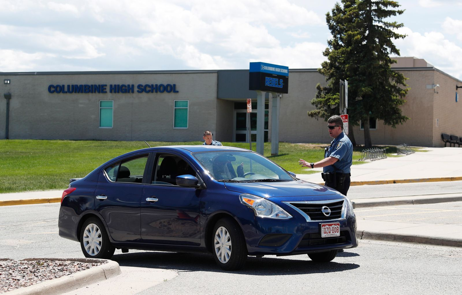 Officers from Jefferson County, Colo., Schools tell a motorist that they can not be on the property of Columbine High School, Thursday, June 13, 2019, in Littleton, Colo. The school district is considering the demolition of Columbine, the scene of a mass assault more than 20 years ago, and rebuilding the current school. (AP Photo/David Zalubowski)