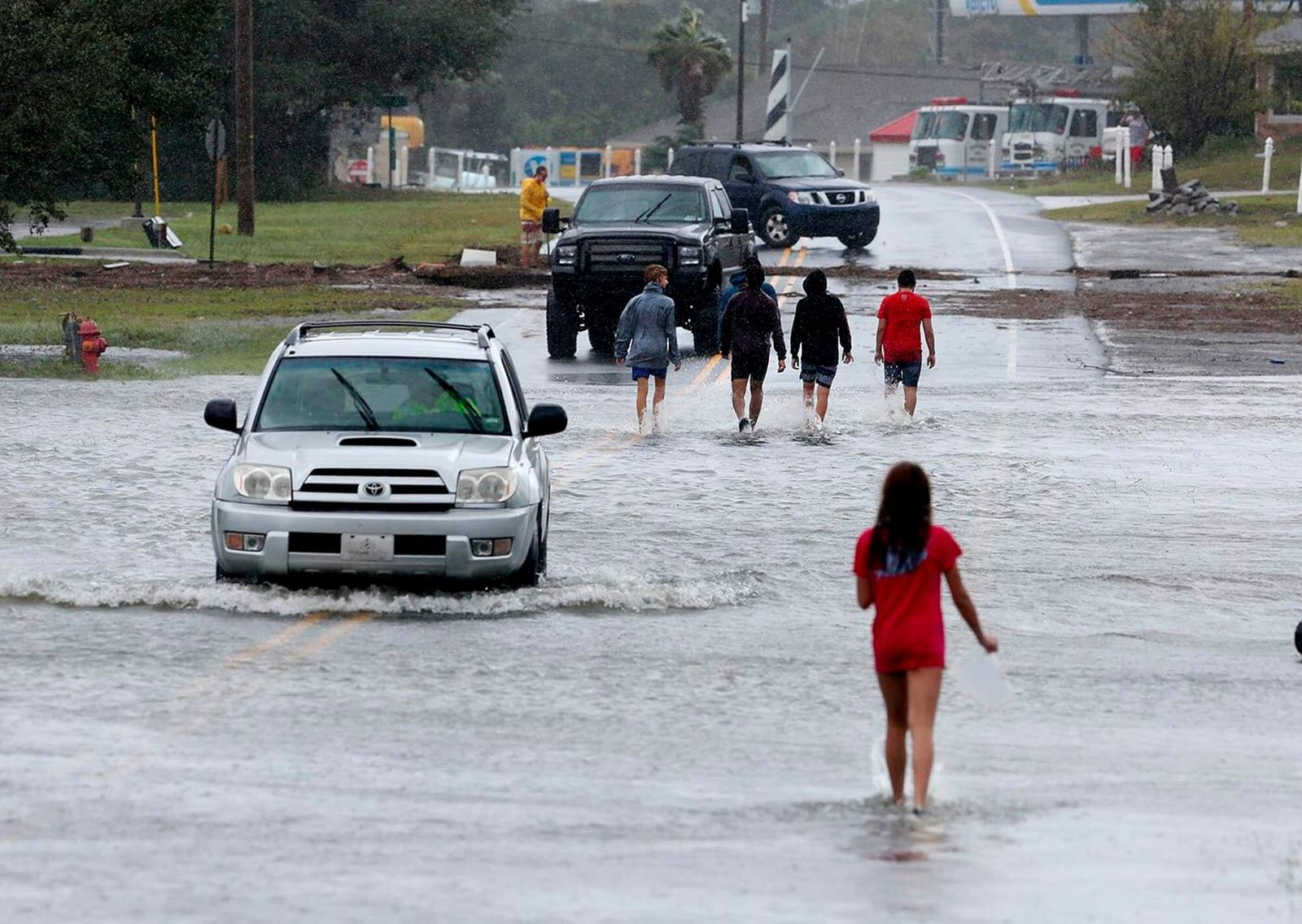 Residents walk and drive through the receding flood waters in Buxton, N.C., after Hurricane Dorian leaves Hatteras Island on Friday, Sept. 6, 2019. (Steve Earley/The Virginian-Pilot via AP)