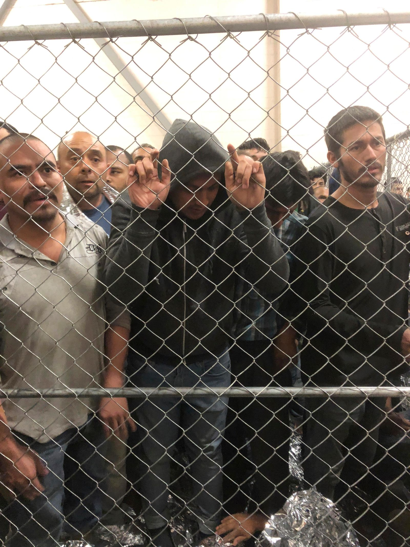 Men stand in a U.S. Immigration and Border Enforcement detention center in McAllen, Texas, Friday, July 12, 2019, as Vice President Mike Pence visits. (Josh Dawsey/The Washington Post via AP)