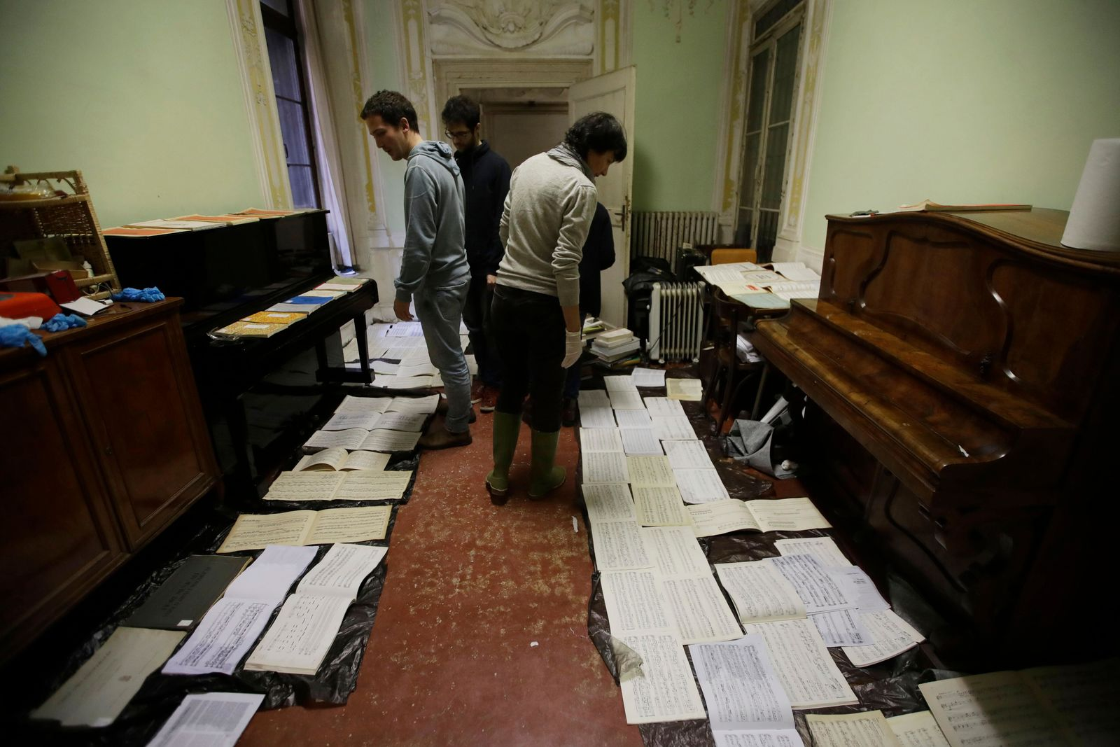 Volunteers try to save ancient music sheets by placing them to dry at the first floor of Venice Conservatory after recovering them from ground floor, Italy, Saturday, Nov. 16, 2019. High tidal waters returned to Venice on Saturday, four days after the city experienced its worst flooding in 50 years. Young Venetians are responding to the worst flood in their lifetimes by volunteering to help salvage manuscripts, clear out waterlogged books and lend a hand where needed throughout the stricken city.(AP Photo/Luca Bruno)