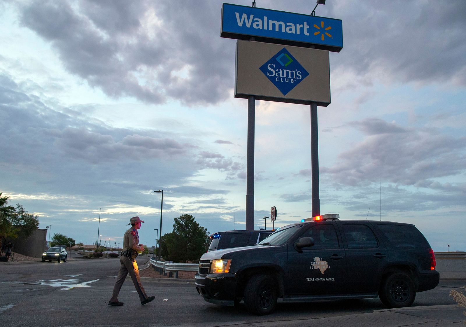 FILE - In this Aug. 4, 2019, file photo a Texas State Trooper walks back to his car while providing security outside the Walmart store in the aftermath of a mass shooting in El Paso, Texas. (AP Photo/Andres Leighton, File)