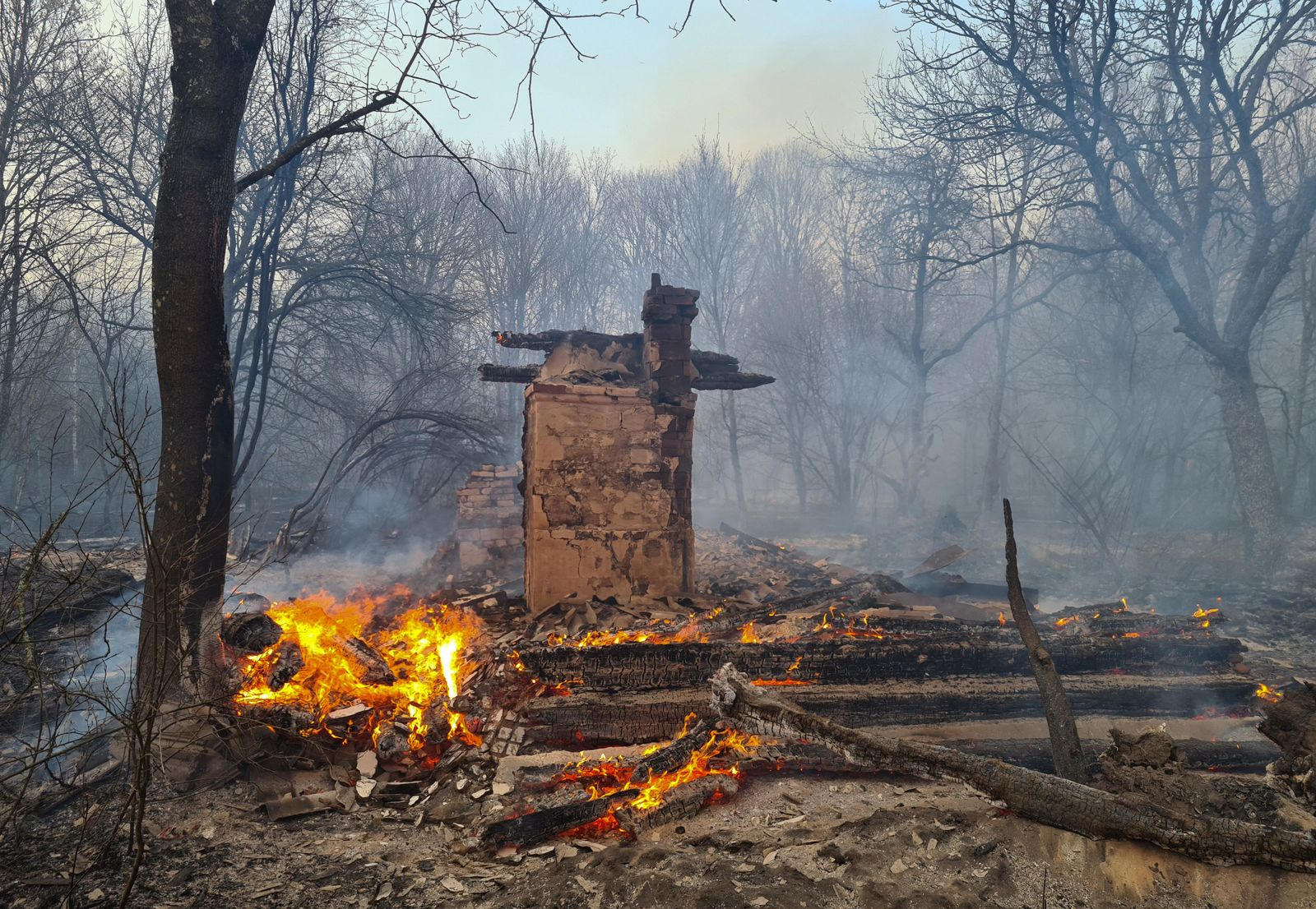An unhabited house burns in the middle of a forest fire near the village of Volodymyrivka, in the exclusion zone around the Chernobyl nuclear power plant, Ukraine, Sunday April 5, 2020.{ } (AP Photo/Yaroslav Yemelianenko)