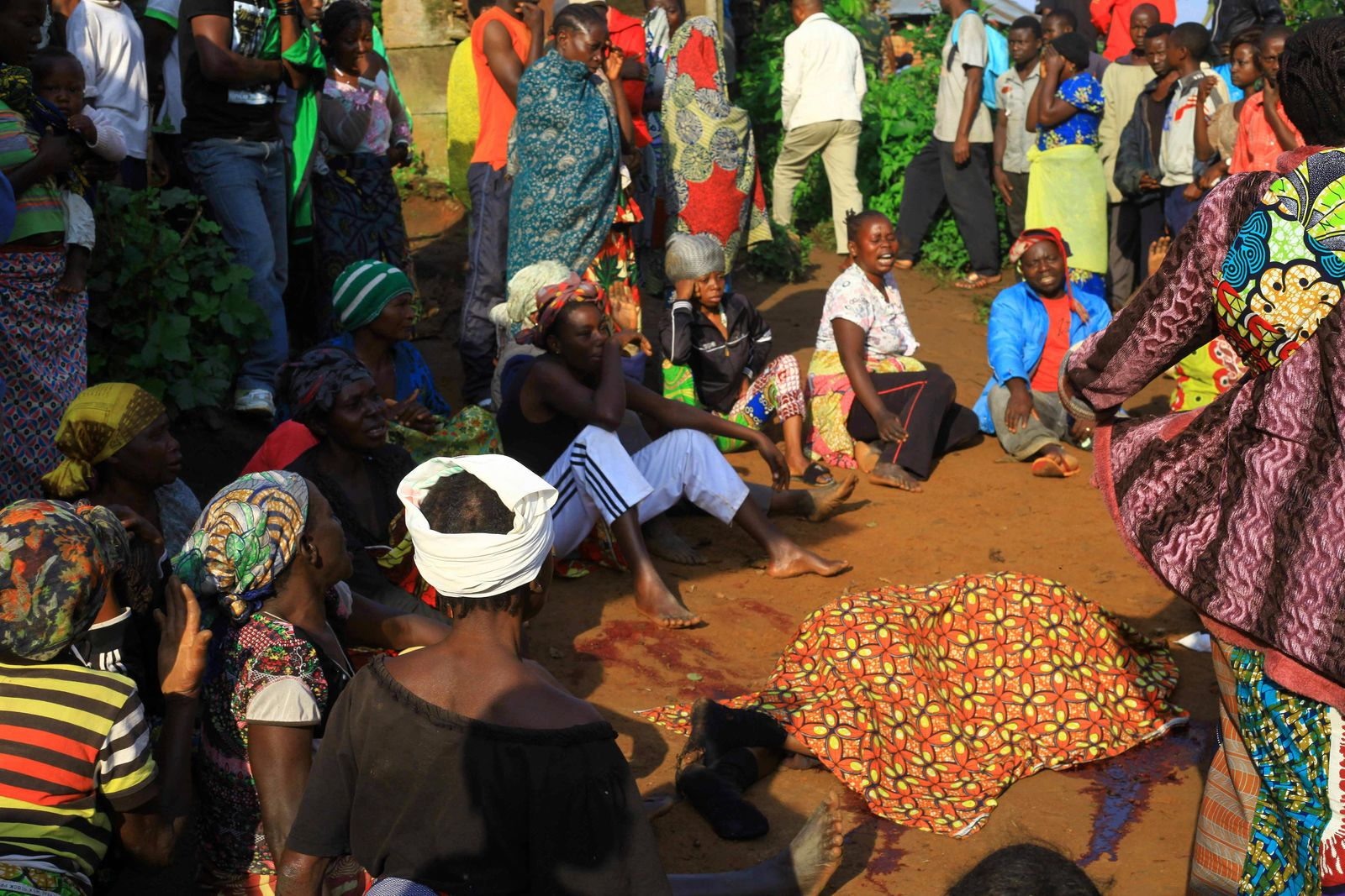 In this photo taken Friday, Oct 5, 2018, family members and onlookers mourn over the bodies of civilian killed by The Allied Democratic Forces rebels in Beni, Eastern Congo. (AP Photo/Al-hadji Kudra Maliro)