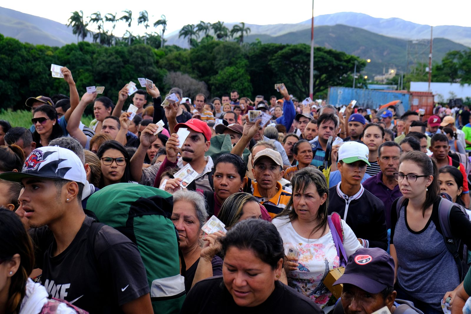 Venezuelans showing their IDs line up to cross the Simon Bolivar international bridge into Cucuta, Colombia, Saturday, June 8, 2019. Venezuela's President Nicolas Maduro ordered the partial re-opening of the border that has been closed since February when he stationed containers on the bridge to block an opposition plan to deliver humanitarian aid into the country. (AP Photo/Ferley Ospina)