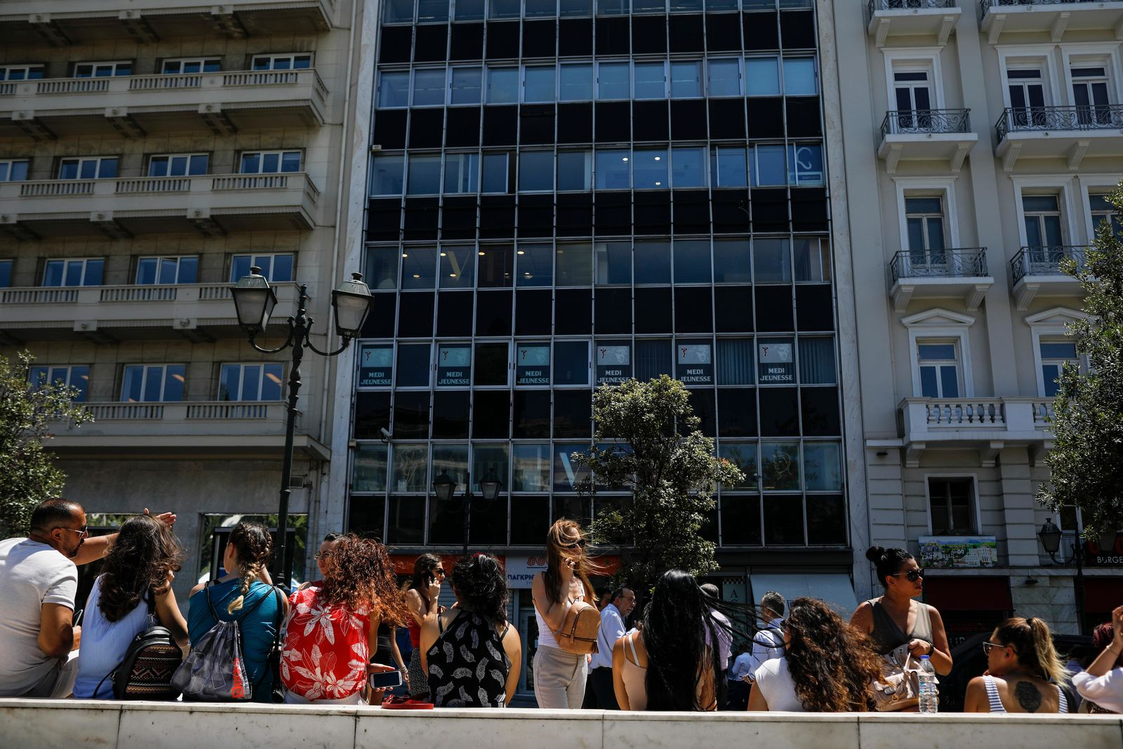 People speak on their phones as they stand outside the building they work in with the Greek Parliament in the background, after a strong earthquake hit near the Greek capital of Athens, Friday, July 19, 2019(AP Photo/Petros Giannakouris)