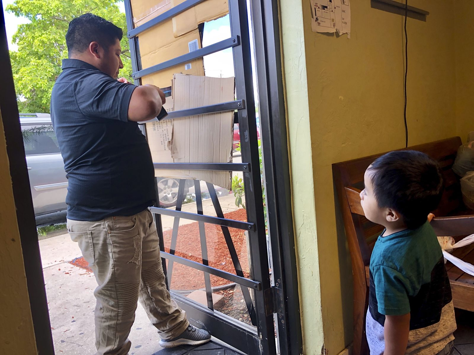 A volunteer of the center is tapes pieces of cardboard to the glass doors as women waited in line for help at the Guatemalan-Maya Center for immigrants on on Friday, Aug. 30, 2019 in  Lake Worth, Fla. (AP PhotoAdriana Gomez)