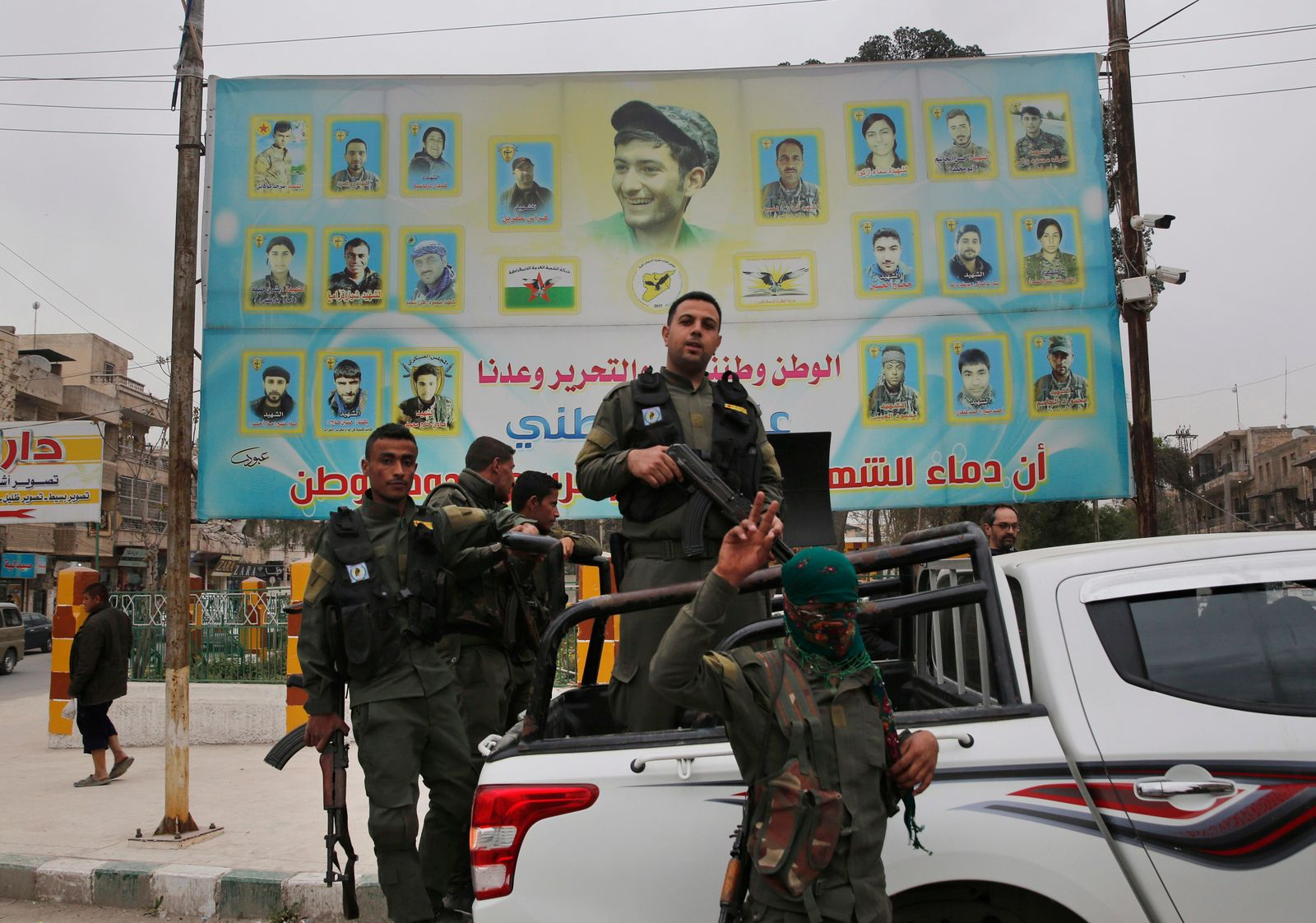 FILE - In this March 28, 2018 file photo, members of the Kurdish internal security forces stand on their vehicle in front of a giant poster showing portraits of fighters killed fighting against the Islamic State group, in Manbij, north Syria. On Friday, Dec. 28, 2018, Syria's military announced it has taken control the flash-point Kurdish-held town of Manbij, where Turkey has threatened an offensive. The announcement Friday came shortly after the main Syrian Kurdish militia invited the government to seize control of Manbij to prevent an attack. (AP Photo/Hussein Malla, File)