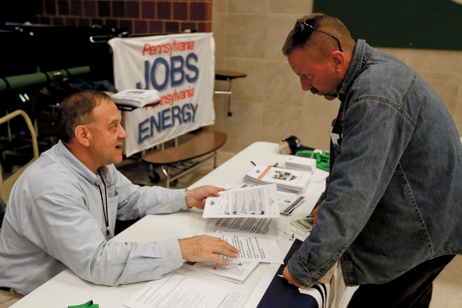 FILE - In this Thursday, Nov. 2, 2017, photo, a recruiter in the shale gas industry, left, speaks with an attendee of a job fair in Cheswick, Pa. (AP Photo/Keith Srakocic, File)