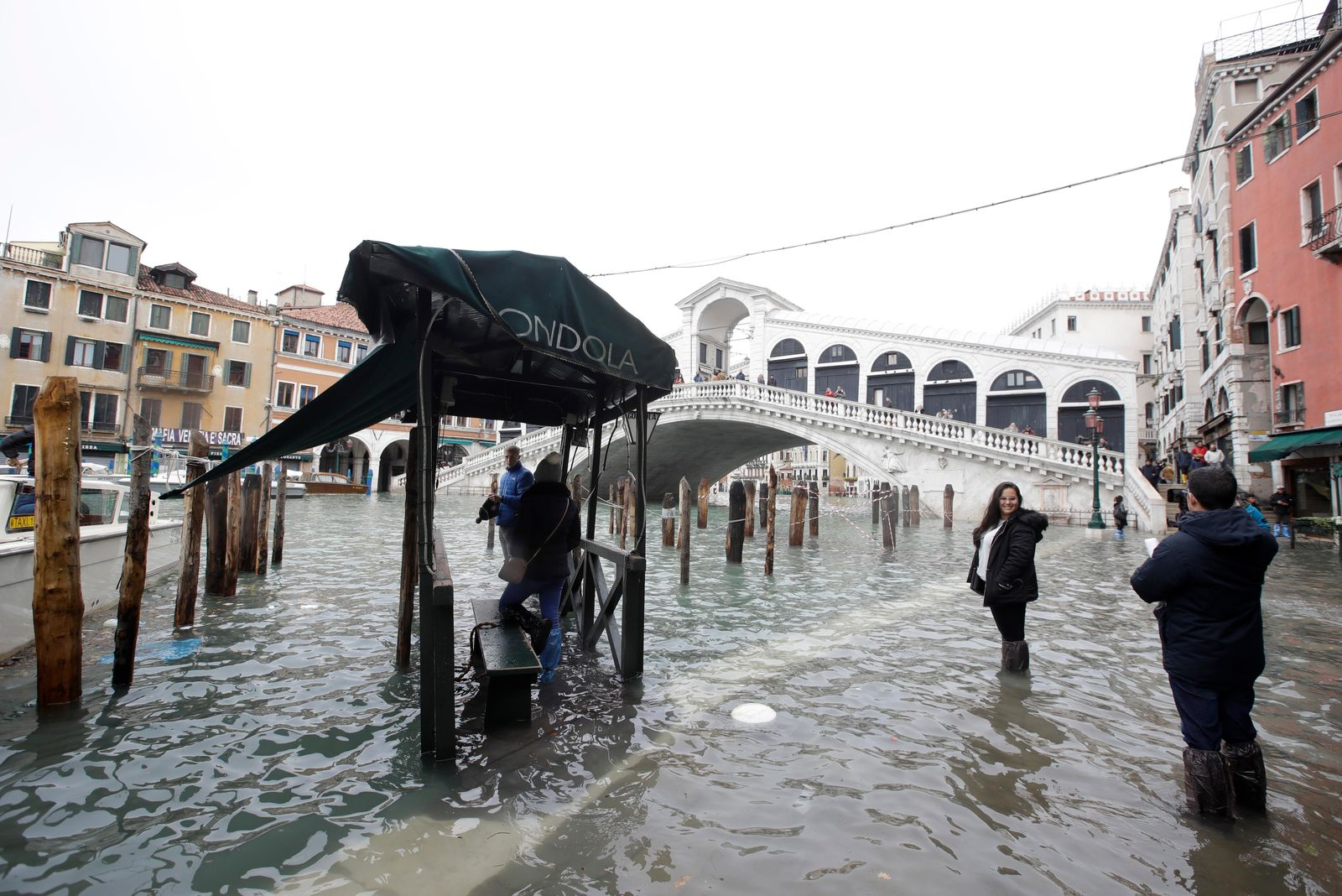 Tourists take pictures in front of the Rialto Bridge while wading through high water, in Venice, Wednesday, Nov. 13, 2019. The high-water mark hit 187 centimeters (74 inches) late Tuesday, Nov. 12, 2019, meaning more than 85% of the city was flooded. The highest level ever recorded was 194 centimeters (76 inches) during infamous flooding in 1966. (AP Photo/Luca Bruno)