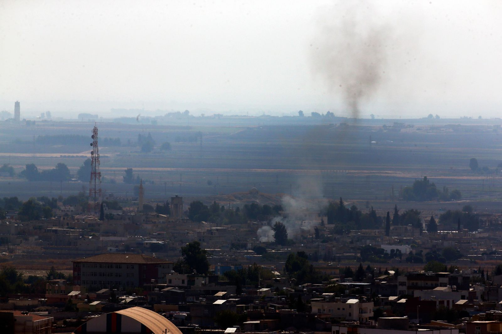 In this photo taken from the Turkish side of the border between Turkey and Syria, in Ceylanpinar, Sanliurfa province, southeastern Turkey, smoke billows from targets in Ras al-Ayn, Syria, caused by shelling by Turkish forces, Friday, Oct. 18, 2019. (AP Photo/Lefteris Pitarakis)