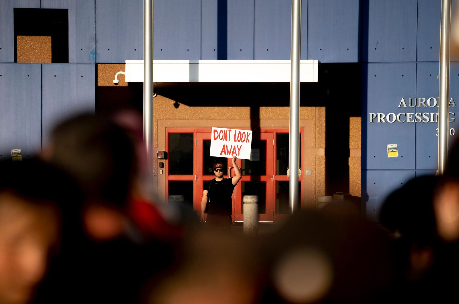 In this Friday, July 12, 2019, photo, a sole protester stands beyond the threshold and on GEO property while hundreds of protesters assembled for a march at the GEO facility, in Aurora, Colo. Police say they will be reviewing any available video to help them identity protesters who trespassed and pulled down the American flag in front of an immigration detention center in suburban Denver, tried to burn it and replaced it with a Mexican flag. (Philip B. Poston/The Aurora Sentinel via AP)