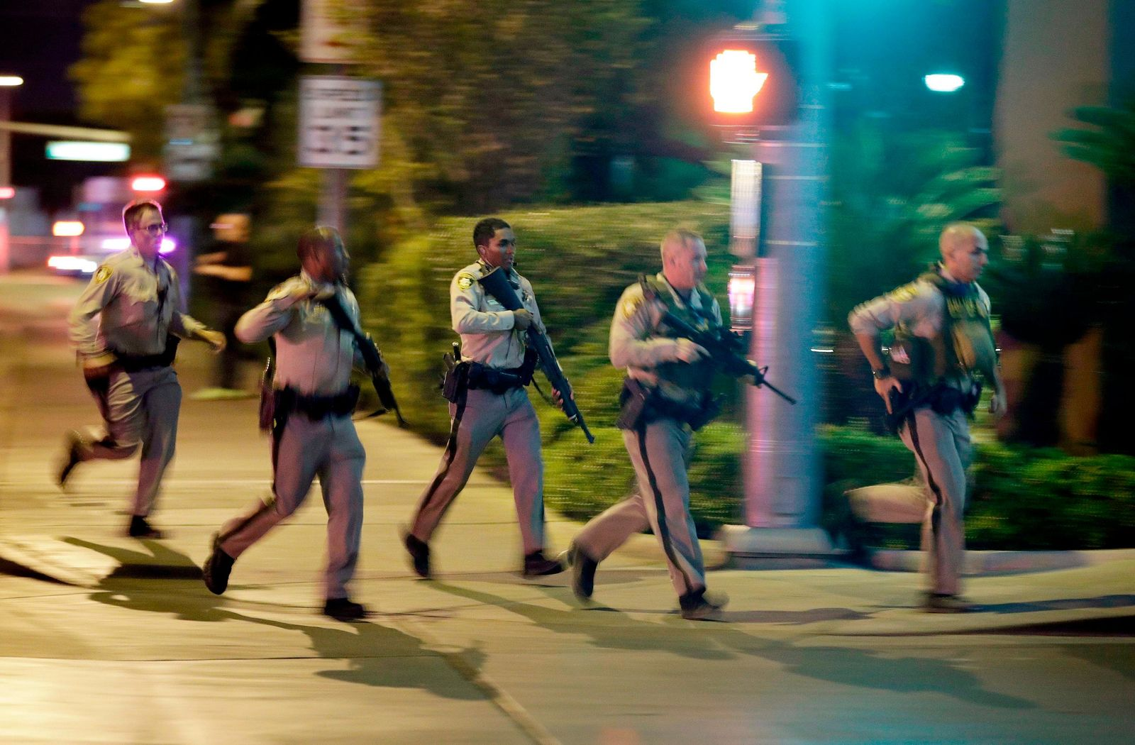 FILE - In this Oct. 1, 2017, file photo, police run toward the scene of a shooting near the Mandalay Bay resort and casino on the Las Vegas Strip in Las Vegas. (AP Photo/John Locher, File)