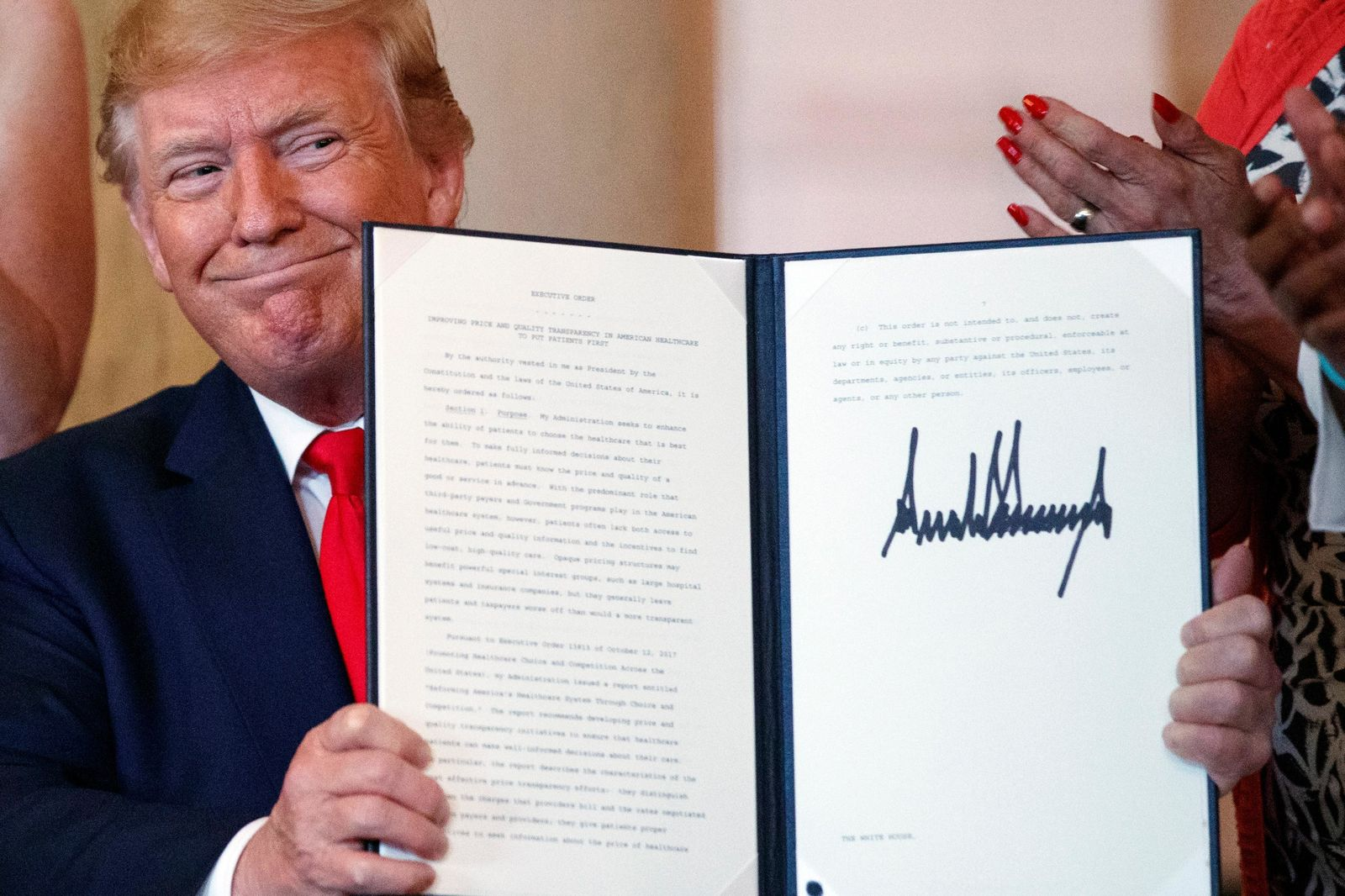 FILE - In this June 24, 2019, file photo, President Donald Trump holds up an executive order during a signing ceremony that calls for upfront disclosure by hospitals of actual prices for common tests and procedures to keep costs down, at the White House in Washington,. Trump is now three for three. Each year of his presidency, he has issued more executive orders than did former President Barack Obama during the same time-span. (AP Photo/Carolyn Kaster, File)