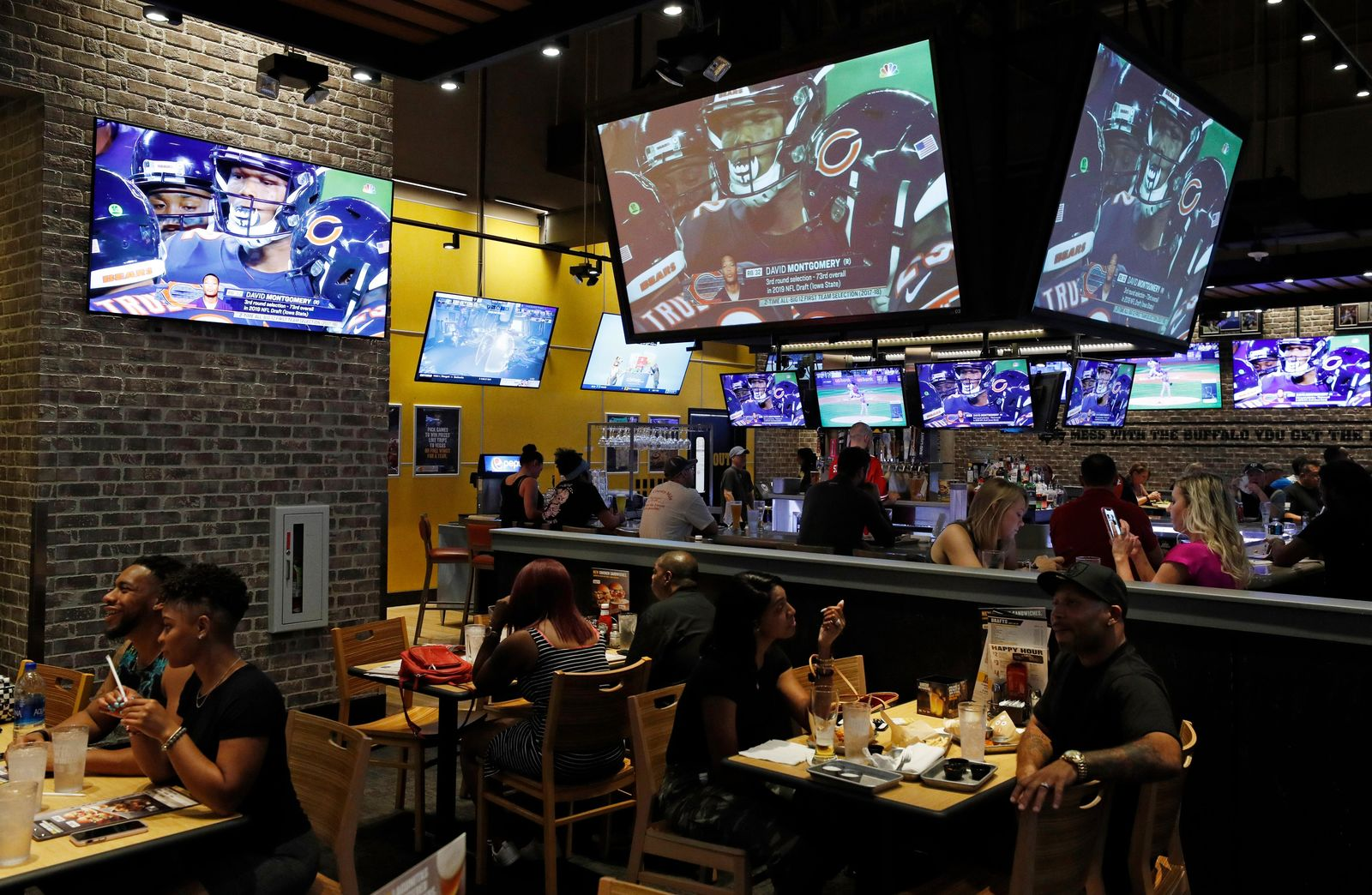 People eat and watch football at a Buffalo Wild Wings, Thursday, Sept. 5, 2019, in Las Vegas.{ } (AP Photo/John Locher)