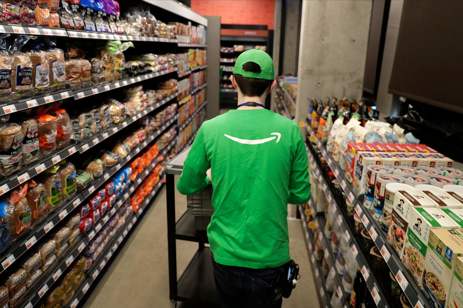 In this Feb. 21, 2020 photo, a worker pushes a cart inside an Amazon Go Grocery store set to open soon in Seattle's Capitol Hill neighborhood.{ } (AP Photo/Ted S. Warren)