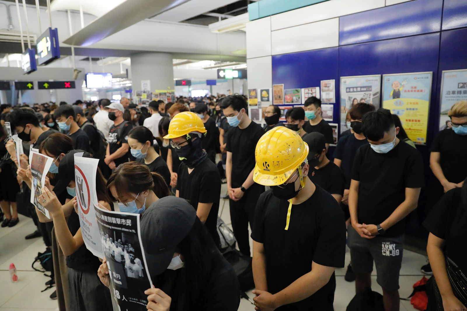"Demonstrators bow their heads in silence during a protest at the Yuen Long MTR station in Hong Kong, Wednesday, Aug. 21, 2019. Japan's top diplomat on Tuesday told his Chinese counterpart that Japan is ""deeply concerned"" about the continuing protests in Hong Kong. (AP Photo/Kin Cheung)"