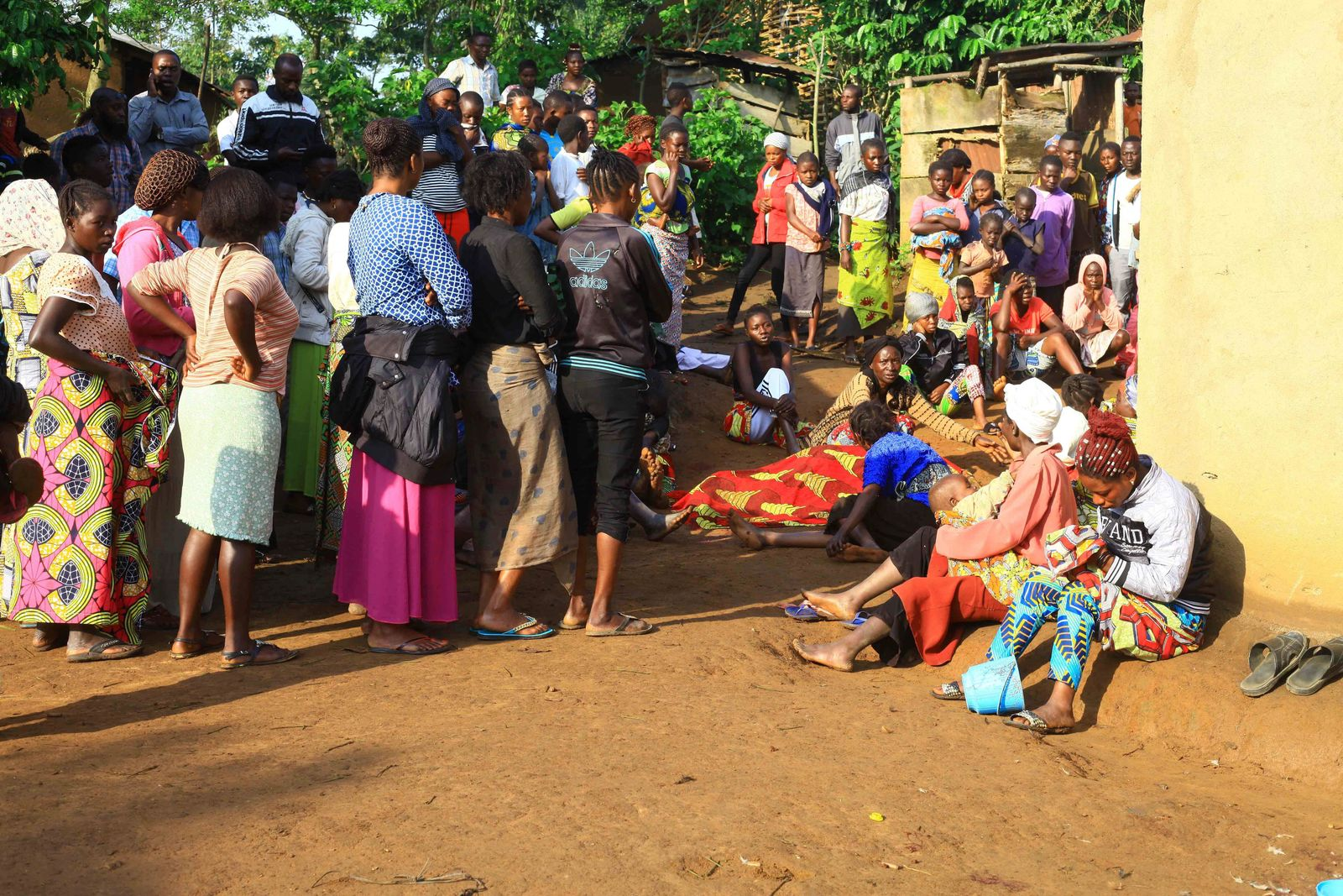 In this photo taken Friday, Oct 5, 2018, family members and onlookers mourn over the bodies of civilians killed by The Allied Democratic Forces rebels in Beni, Eastern Congo. (AP Photo/Al-hadji Kudra Maliro)
