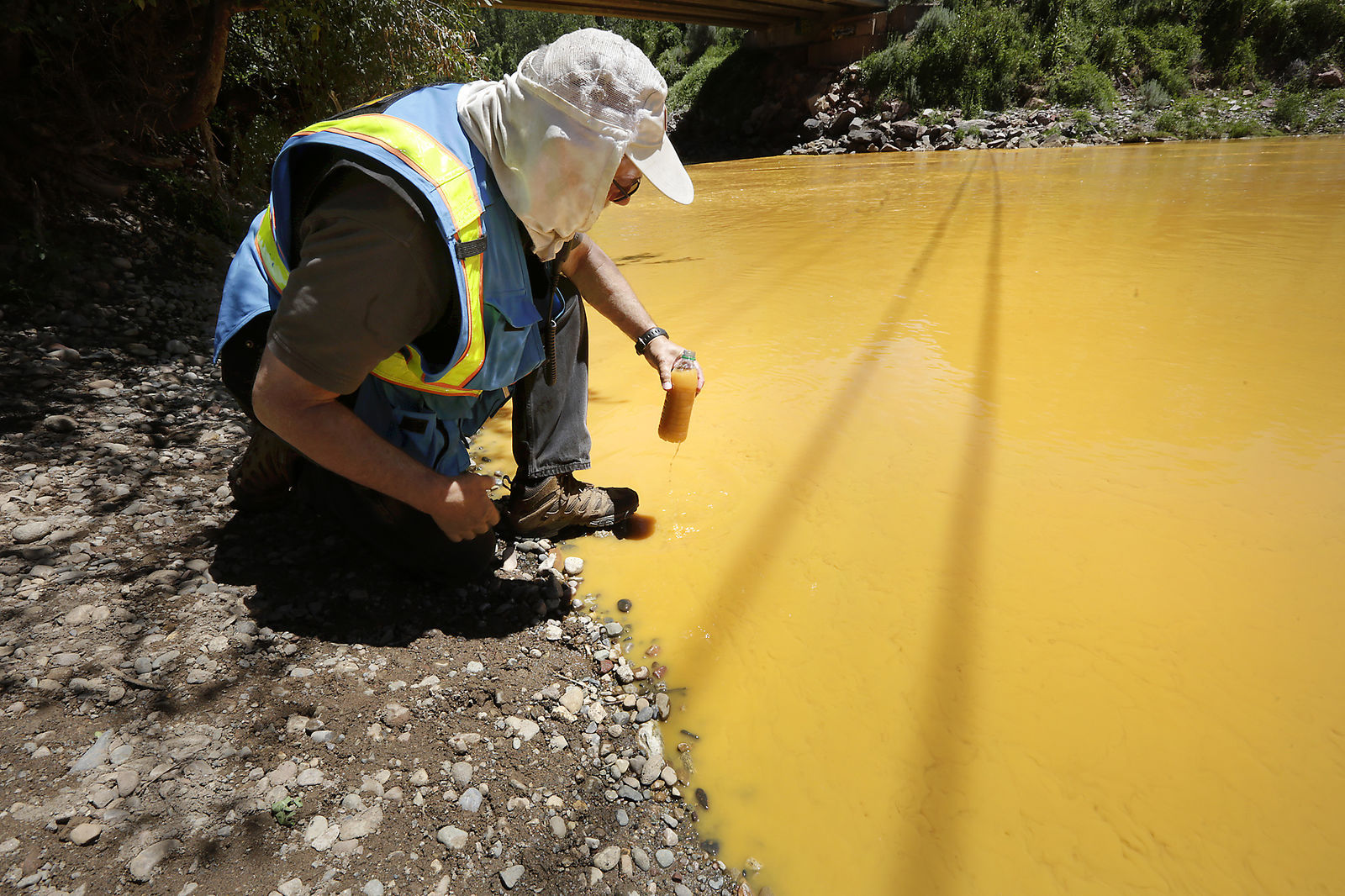 FILE - In this Aug. 6, 2015 file photo, Dan Bender, with the La Plata County Sheriff's Office, takes a water sample from the Animas River near Durango, Colo. after the accidental released of an estimated 3 million gallons of waste from the Gold King Mine by a crew led by the Environmental Protection Agency. The EPA says it has almost finished reviewing hundreds of damage claims from the spill, but the agency has still not released a clear accounting of the claims made for economic losses and personal injuries. (Jerry McBride /The Durango Herald via AP, File)