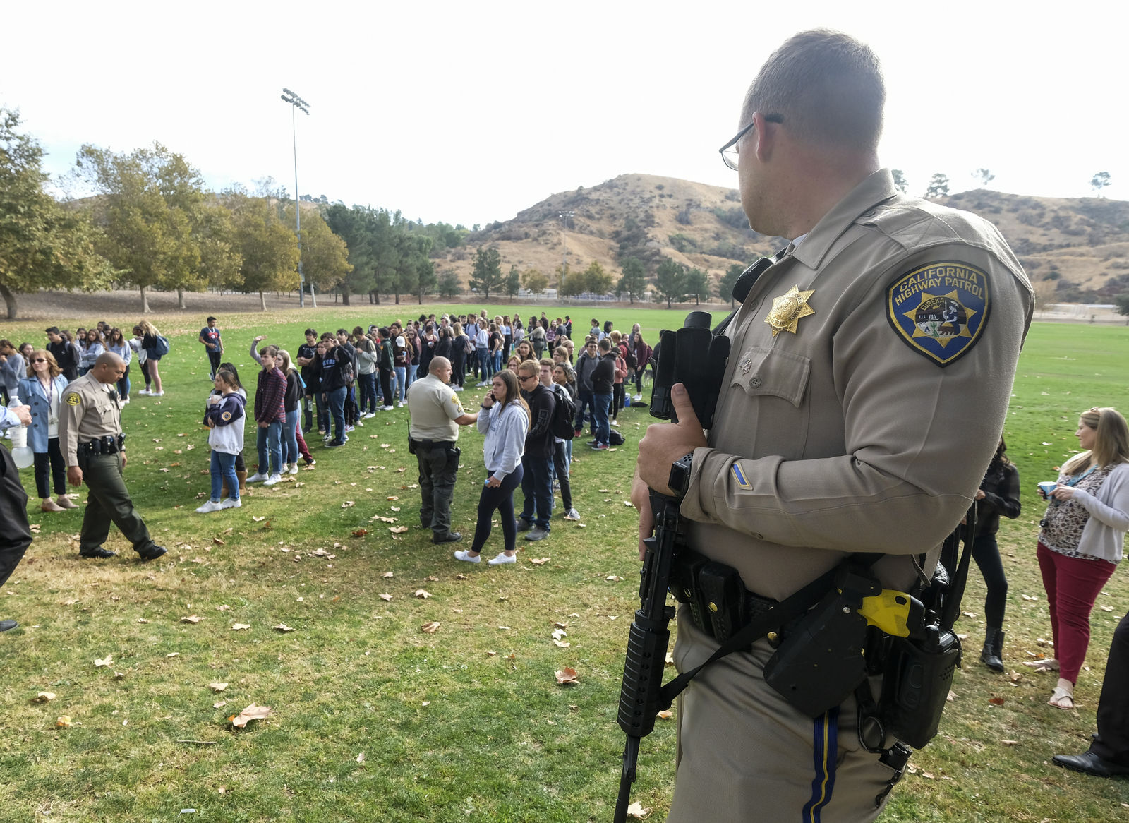 A police officer stands guard as students wait to be reunited with their parents following a shooting at Saugus High School that injured several people, Thursday, Nov. 14, 2019, in Santa Clarita, Calif. (AP Photo/Ringo H.W. Chiu)