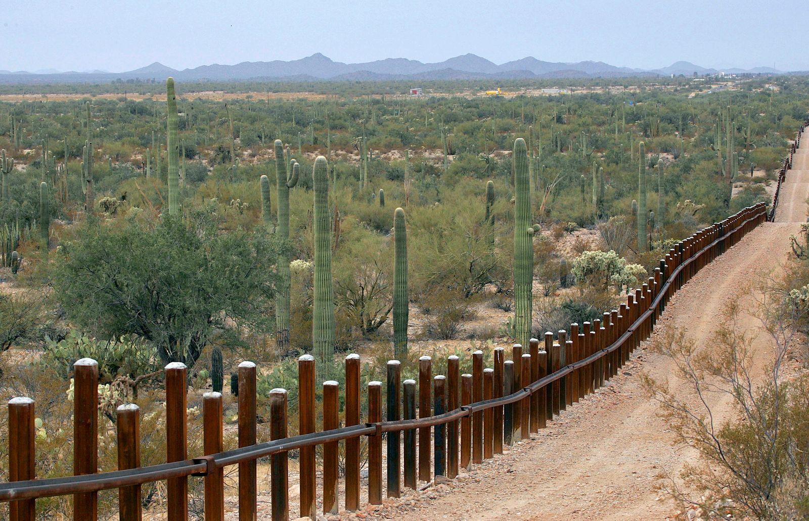 FILE - This Feb. 17, 2006 file photo shows the international border line made up of bollards: irregular, concrete-filled steel poles, seperating Mexico, left from the United States, in the Organ Pipe National Monument near Lukeville, Ariz. The federal government plans on replacing barriers through 100 miles of the southern border in California and Arizona, including through a this national monument and a wildlife refuge, according to government documents and environmental advocates. The Department of Homeland Security on Tuesday waived environmental and dozens of other laws to build more barriers along the southern border. (AP Photo/Matt York, File)