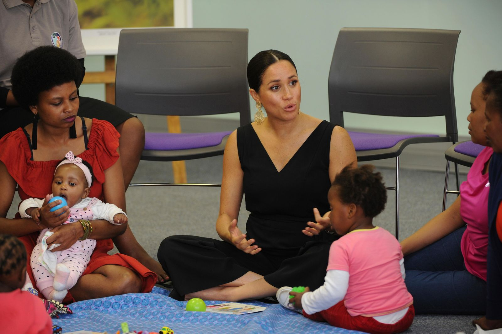 FILE - In this Wednesday, Sept. 25, 2019 file photo, Britain's Meghan, Duchess of Sussex, centre, talks with mothers during her visit to the Mothers2Mothers organisation, which trains and employs women living with HIV as frontline health workers across eight African nations, in Cape Town, South Africa. The final day of Prince Harry and his wife Meghan's 10-day visit to Africa with infant son Archie in tow has been overshadowed by a lawsuit she has filed against Britain's Mail on Sunday tabloid.  (Henk Kruger/Pool via AP, File)