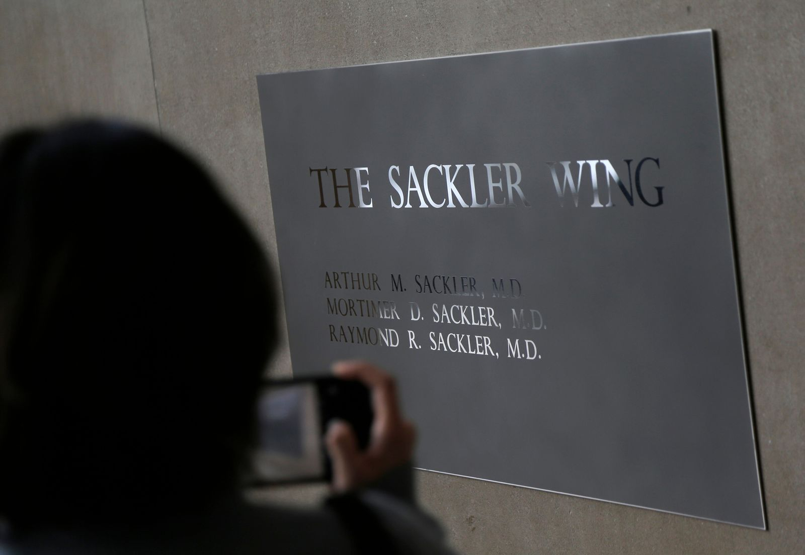 FILE - In this Jan. 17, 2019, file photo, a sign with some names of the Sackler family is displayed at the Metropolitan Museum of Art in New York. Their name used to be on a wing at the Louvre. But now the Sackler family wealth has become linked to sales of OxyContin, and their company, drug maker Purdue Pharma, is attempting to settle lawsuits over the opioid crisis. (AP Photo/Seth Wenig, File)
