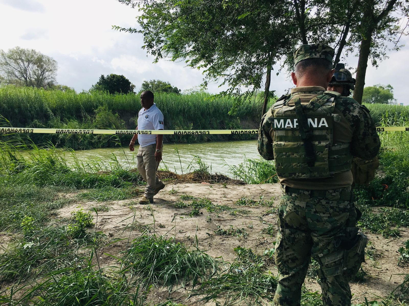 Mexican authorities walk along the Rio Grande bank where the bodies of Salvadoran migrant Oscar Alberto Martínez Ramírez and his nearly 2-year-old daughter Valeria were found, in Matamoros, Mexico, Monday, June 24, 2019, after they drowned trying to cross the river to Brownsville, Texas. Martinez' wife, Tania told Mexican authorities she watched her husband and child disappear in the strong current. (AP Photo/Julia Le Duc)
