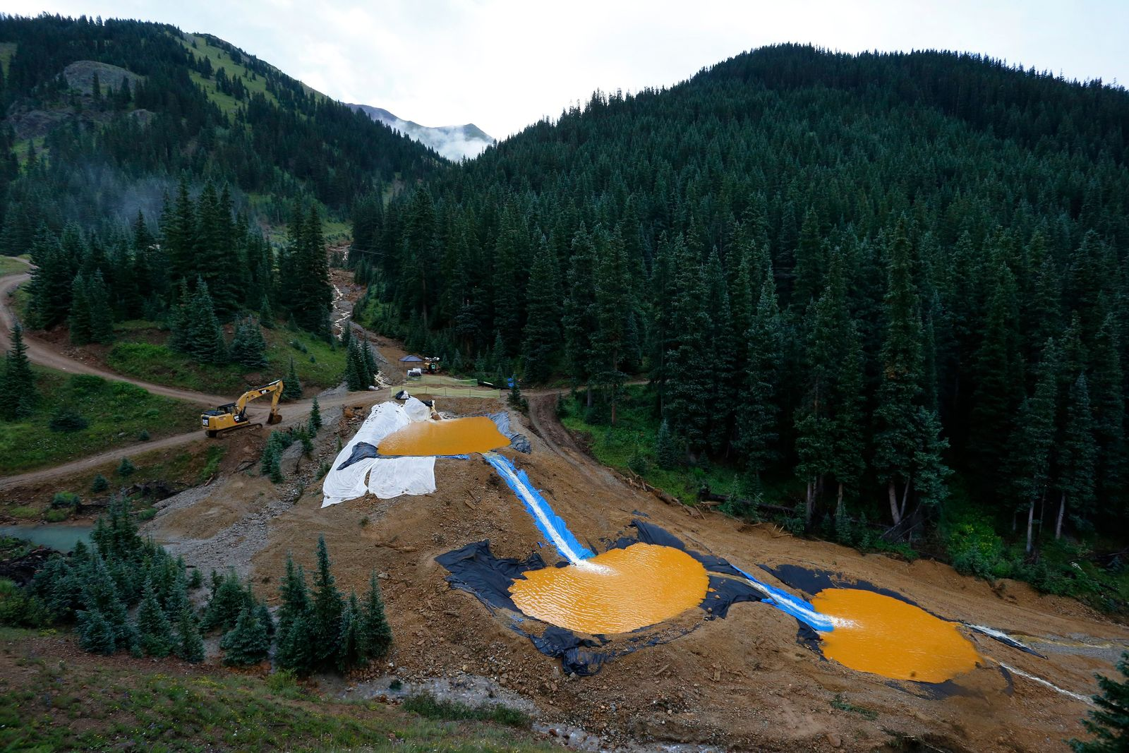 FILE - In this Aug. 12, 2015, file photo, water flows through a series of retention ponds built to contain and filter out heavy metals and chemicals from the Gold King mine accident outside Silverton, Colo.{ } (AP Photo/Brennan Linsley, File)
