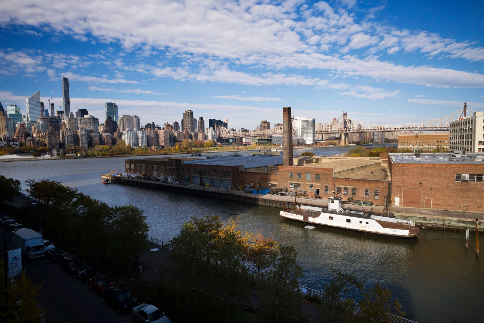 FILE- In this Nov. 7, 2018, file photo, a rusting ferryboat is docked next to an aging industrial warehouse on Long Island City's Anable Basin in the Queens borough of New York. (AP Photo/Mark Lennihan, File)