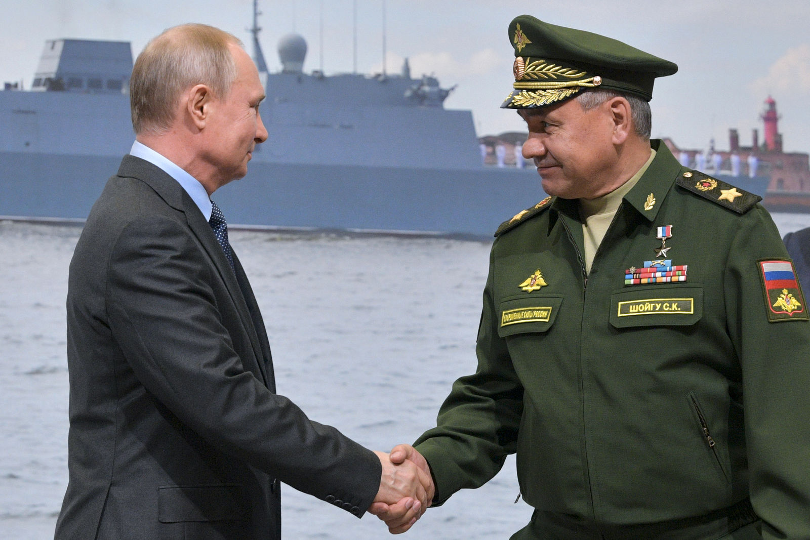 Russian President Vladimir Putin, left, and Russian Defense Minister Sergei Shoigu shake hands during a visit a shipyard in St. Petersburg, Russia, Tuesday, April 23, 2019. Putin said the government will pursue an ambitious navy modernization effort. (Alexei Druzhinin, Sputnik, Kremlin Pool Photo via AP)