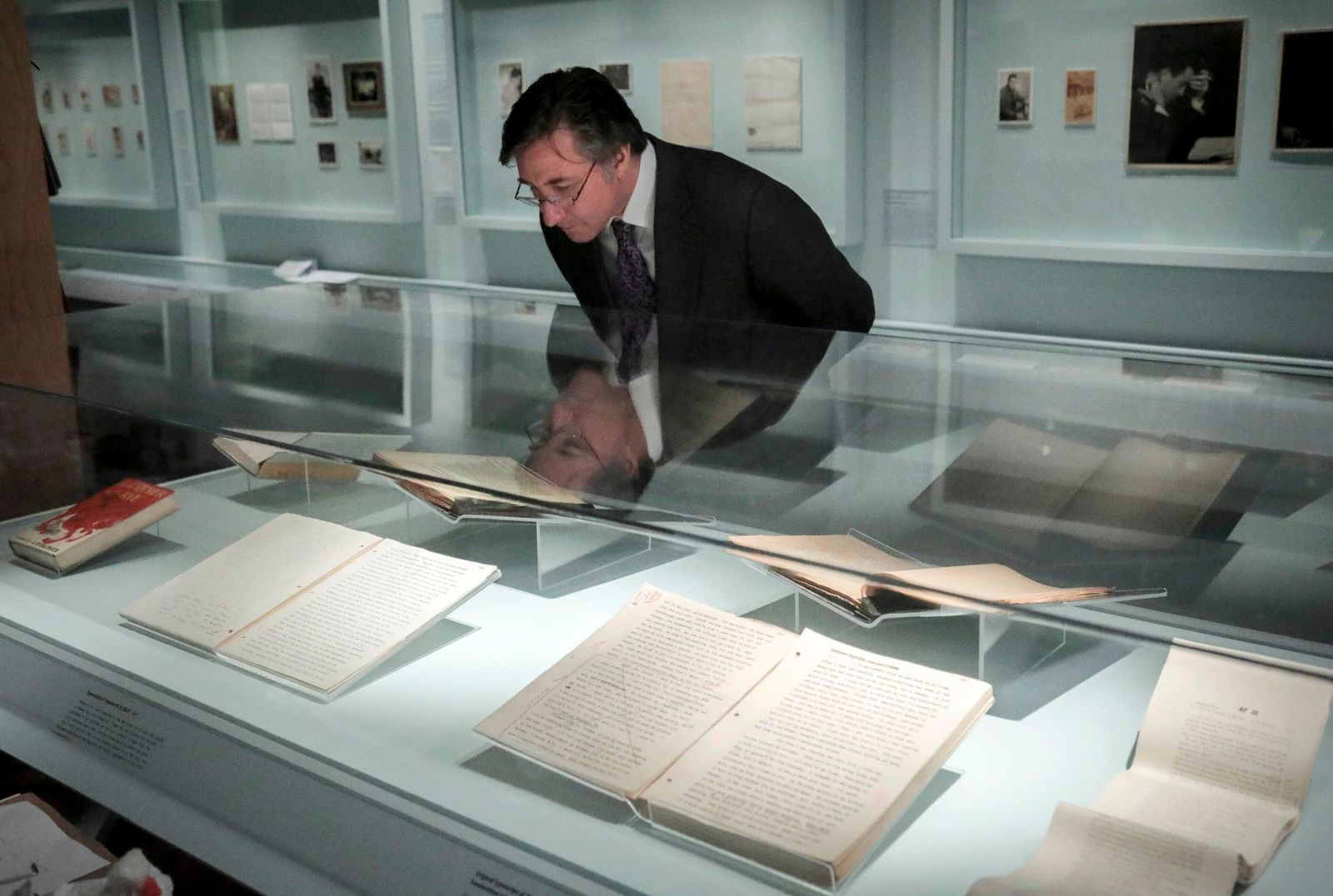 "Declan Kiely, director of special collections and exhibitions at the New York Public Library, review manuscripts during the installation of the library's J.D. Salinger exhibit, Wednesday, Oct. 16, 2019, in New York. The exhibit, titled ""JD Salinger,"" opens Friday and draws from archives made available by the author's family and helps mark the centennial of his birth. (AP Photo/Bebeto Matthews)"