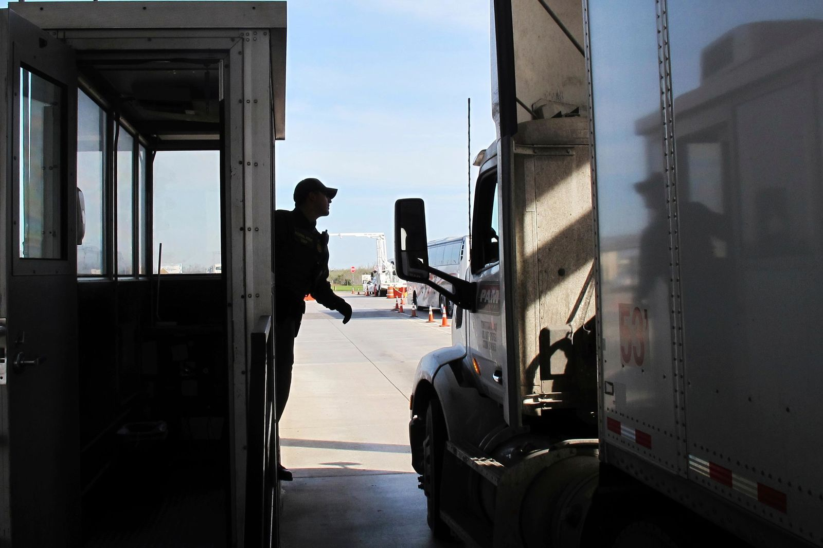 Border Patrol agent Eric Mendoza speaks to the driver of a tractor-trailer passing through the Laredo North vehicle checkpoint in Laredo, Texas, on Friday, Feb. 2, 2018. Smugglers routinely pack people entering the country illegally or drugs into tractor-trailers, counting on the vehicles not being opened at the inspection site. (AP Photo/Nomaan Merchant)