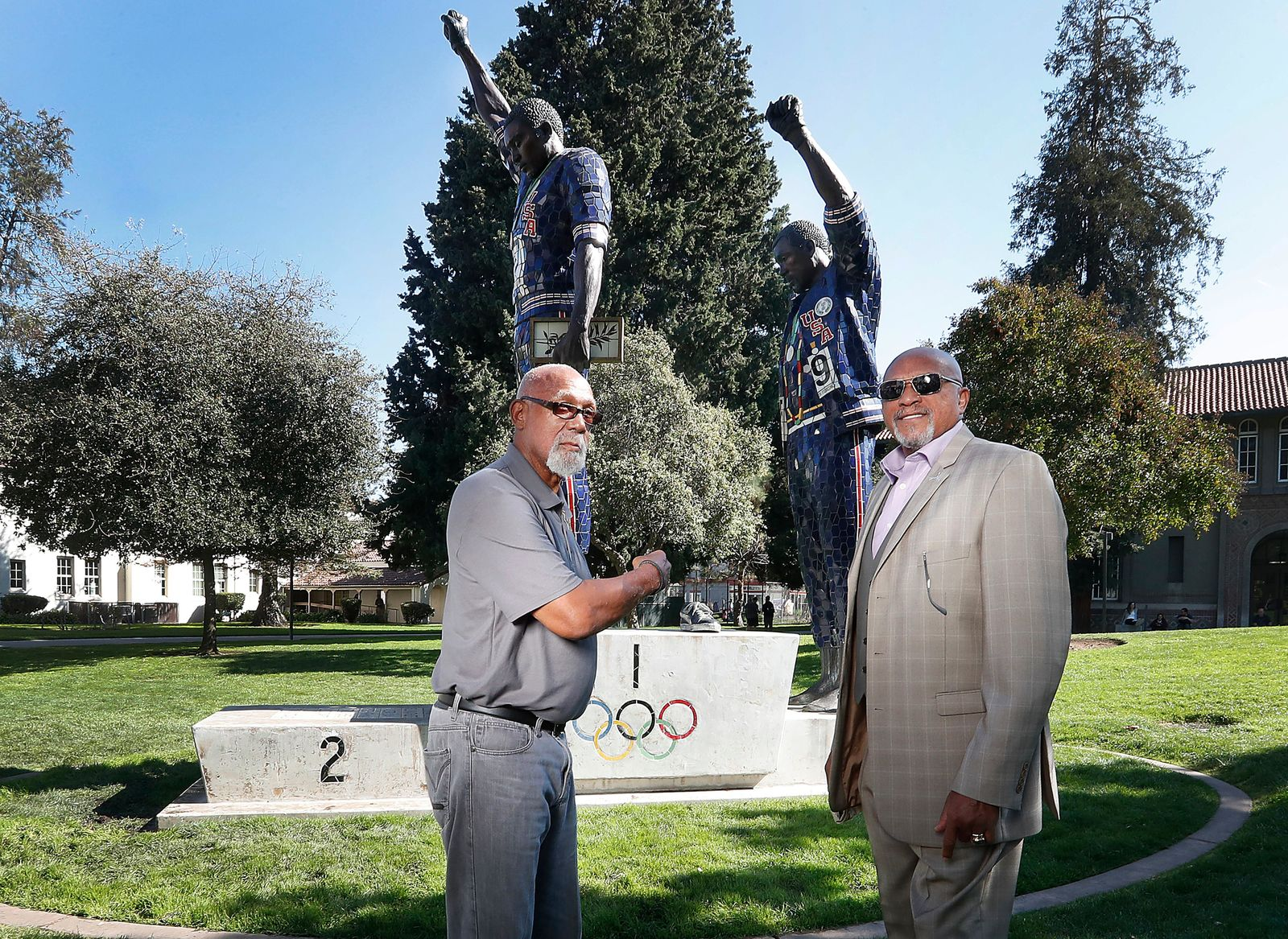 FILE - In this Oct. 17, 2018, file photo, John Carlos, left, and Tommie Smith pose for a photo in front of statue that honors their iconic, black-gloved protest at the 1968 Olympic Games, on the campus of San Jose State University in San Jose, Calif. (AP Photo/Tony Avelar, File)