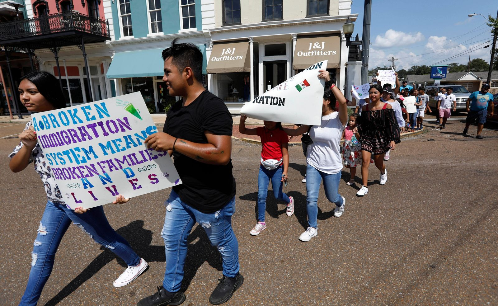 FILE - In this Aug. 11, 2019 photo, children of mainly Latino immigrant parents hold signs in support of them and those individuals picked up during an immigration raid at a food processing plant in Canton, Miss., following a Spanish Mass at Sacred Heart Catholic Church in Canton, Miss. Trump administration rules that could deny green cards to immigrants if they use Medicaid, food stamps, housing vouchers or other forms of public assistance are going into effect. (AP Photo/Rogelio V. Solis)