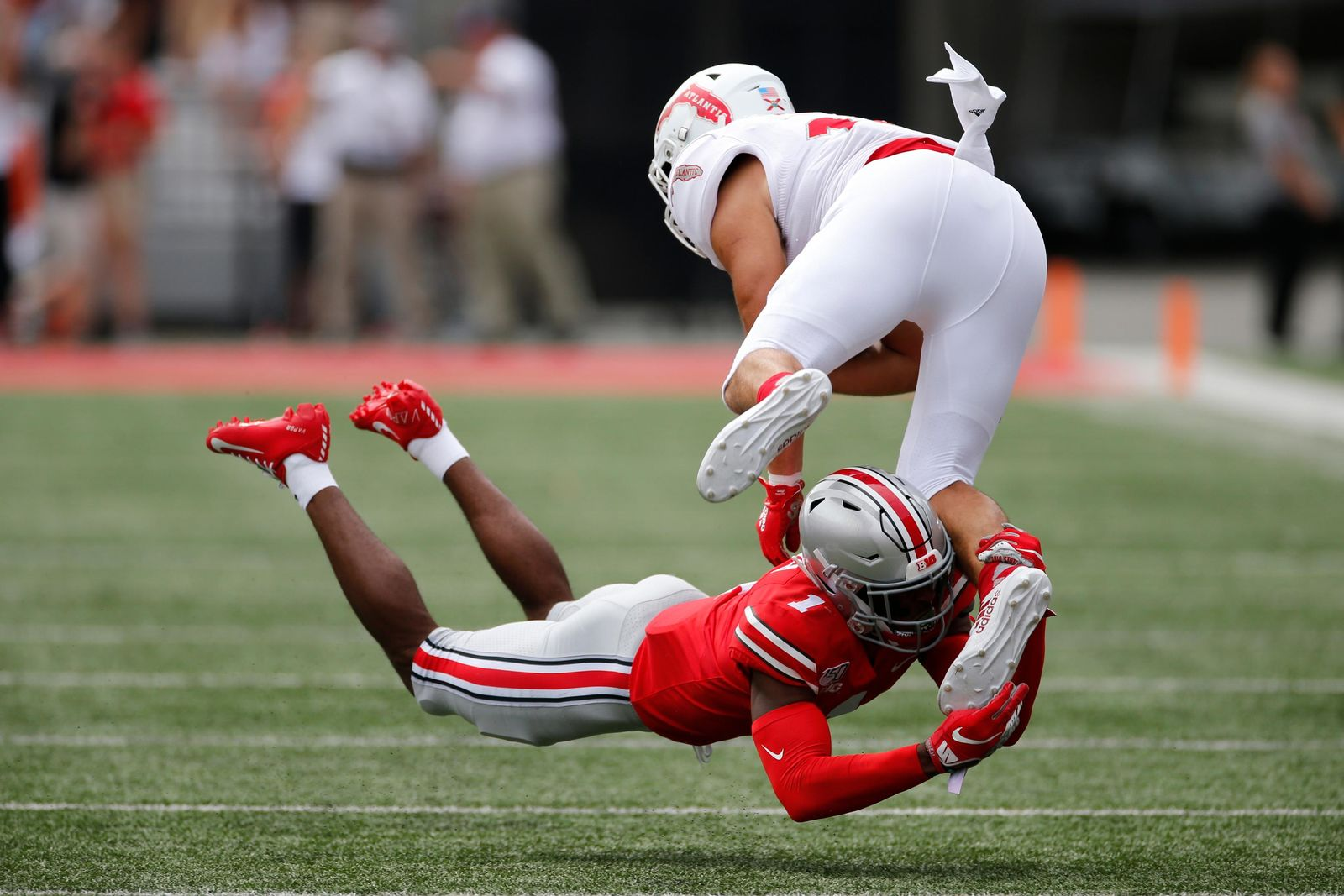 Ohio State defensive back Jeff Okudah, bottom, tackles Florida Atlantic tight end Harrison Bryant during the first half of an NCAA college football game Saturday, Aug. 31, 2019, in Columbus, Ohio. (AP Photo/Jay LaPrete)
