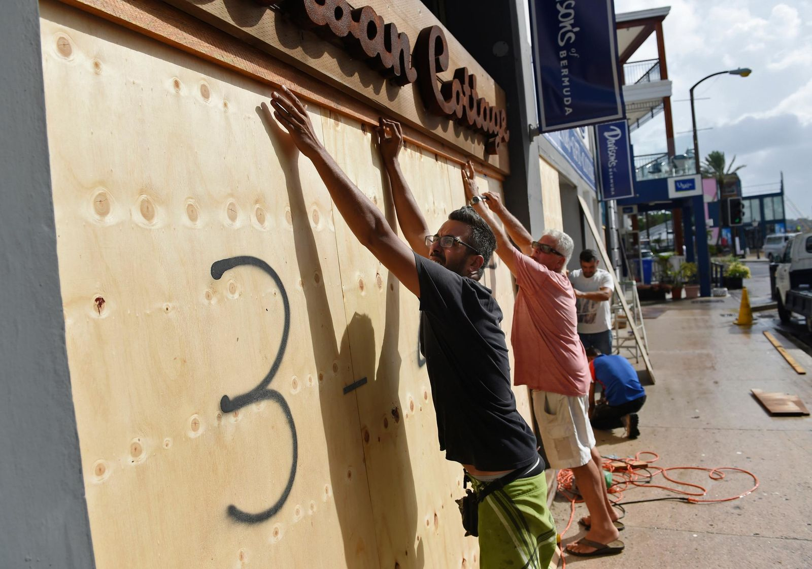 People board up an Urban Cottage store in preparation for Hurricane Humberto in Hamilton, Bermuda, Wednesday, Sept. 18, 2019. Bermuda's government called up troops and urged people on the British Atlantic island to make final preparations for an expected close brush Wednesday with Hurricane Humberto, a powerful Category 3 storm. Authorities ordered early closings of schools, transportation and government offices. (AP Photo/Akil J. Simmons)