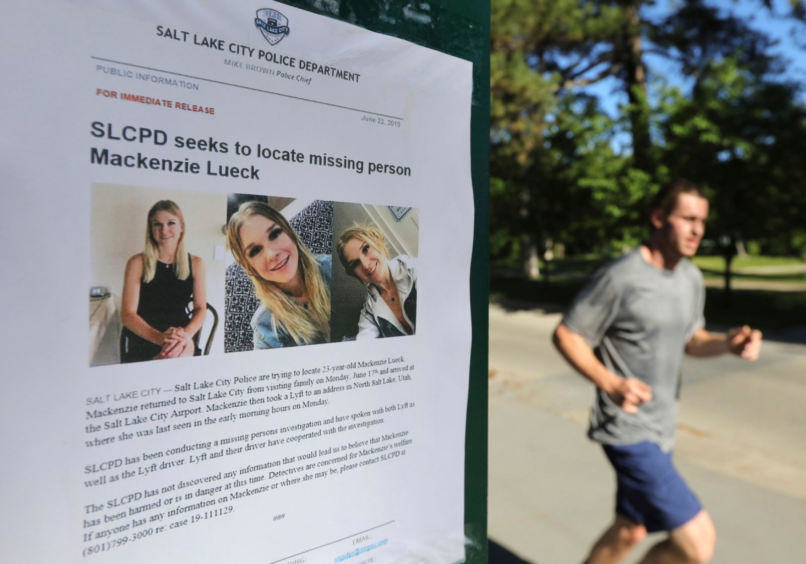 CORRECTS SPELLING OF LUECK - A joggers runs pass a poster of MacKenzie Lueck at Liberty Park Monday, June 24, 2019, in Salt Lake City. Police and friends are investigating the disappearance of the 23-year-old University of Utah student, whose last communication with her family said she arrived at Salt Lake City International Airport on Monday, June 17. (AP Photo/Rick Bowmer)