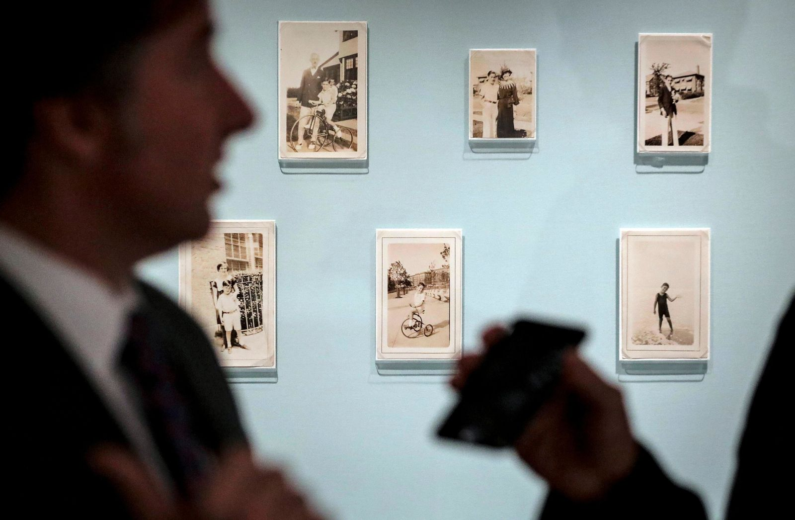 Declan Kiely, director of special collections and exhibitions at the New York Public Library, gives an interview next to childhood photographs of author J.D. Salinger, Wednesday, Oct. 16, 2019, in New York.{ } (AP Photo/Bebeto Matthews)