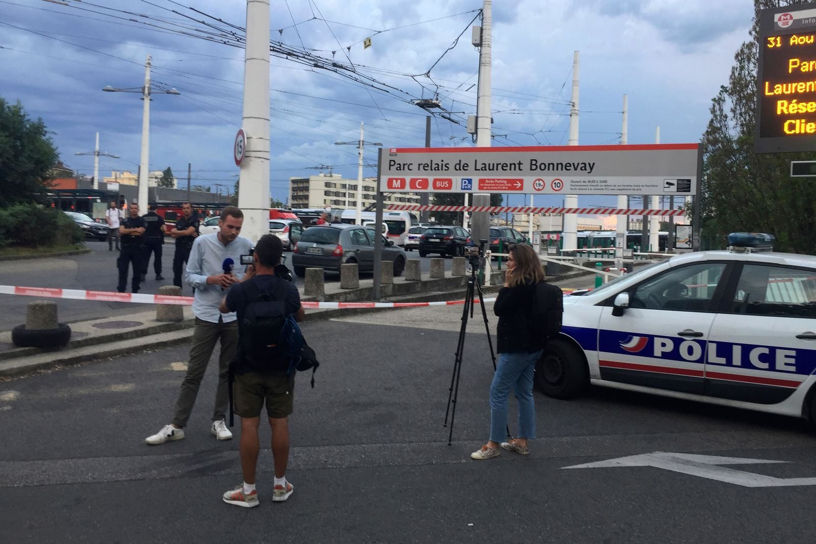 Reporters work near a subway station after an assailant stabbed one person to death and injured nine others, Saturday Aug.31, 2019 just outside a subway station in Villeurbanne, outside Lyon, central France. The reason for the attack is unclear. (AP Photo/Nicolas Vaux-Montagny)