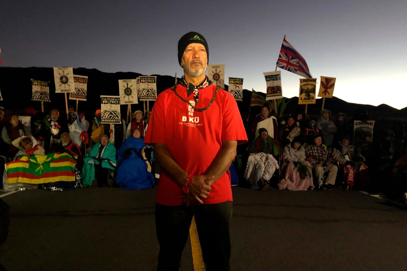 Dexter Kaiama, center, joins demonstrators gathered to block a road at the base of Hawaii's tallest mountain, Monday, July 15, 2019, in Mauna Kea, Hawaii, to protest the construction of a giant telescope on land that some Native Hawaiians consider sacred. (AP Photo/Caleb Jones)