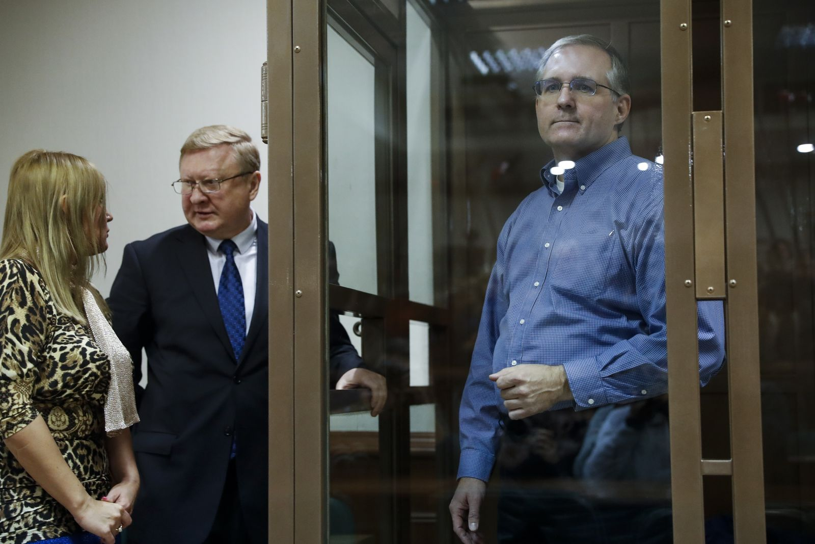 Paul Whelan, a former U.S. Marine, who was arrested in Moscow at the end of last year, right, looks through a cage's glass as his lawyers talk to each other in a court room in Moscow, Russia, Tuesday, Jan. 22, 2019. (AP Photo/Pavel Golovkin)