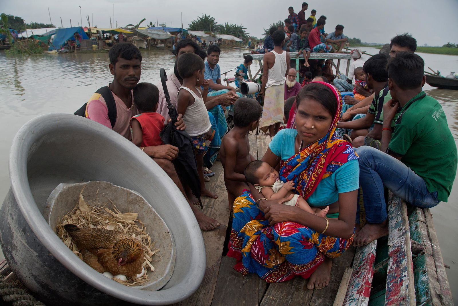 Indian woman Amena Khatoon, 22, holding her two month old baby girl Umahani sits on a boat as a hen hatches its eggs in a container as flood affected villagers travel on a boat in Katahguri village along the river Brahmaputra, east of Gauhati, India, Sunday, July 14, 2019. Officials in northeastern India said more than a dozen people were killed and over a million affected by flooding. Rain-triggered floods, mudslides and lightning have left a trail of destruction in other parts of South Asia. (AP Photo/Anupam Nath)