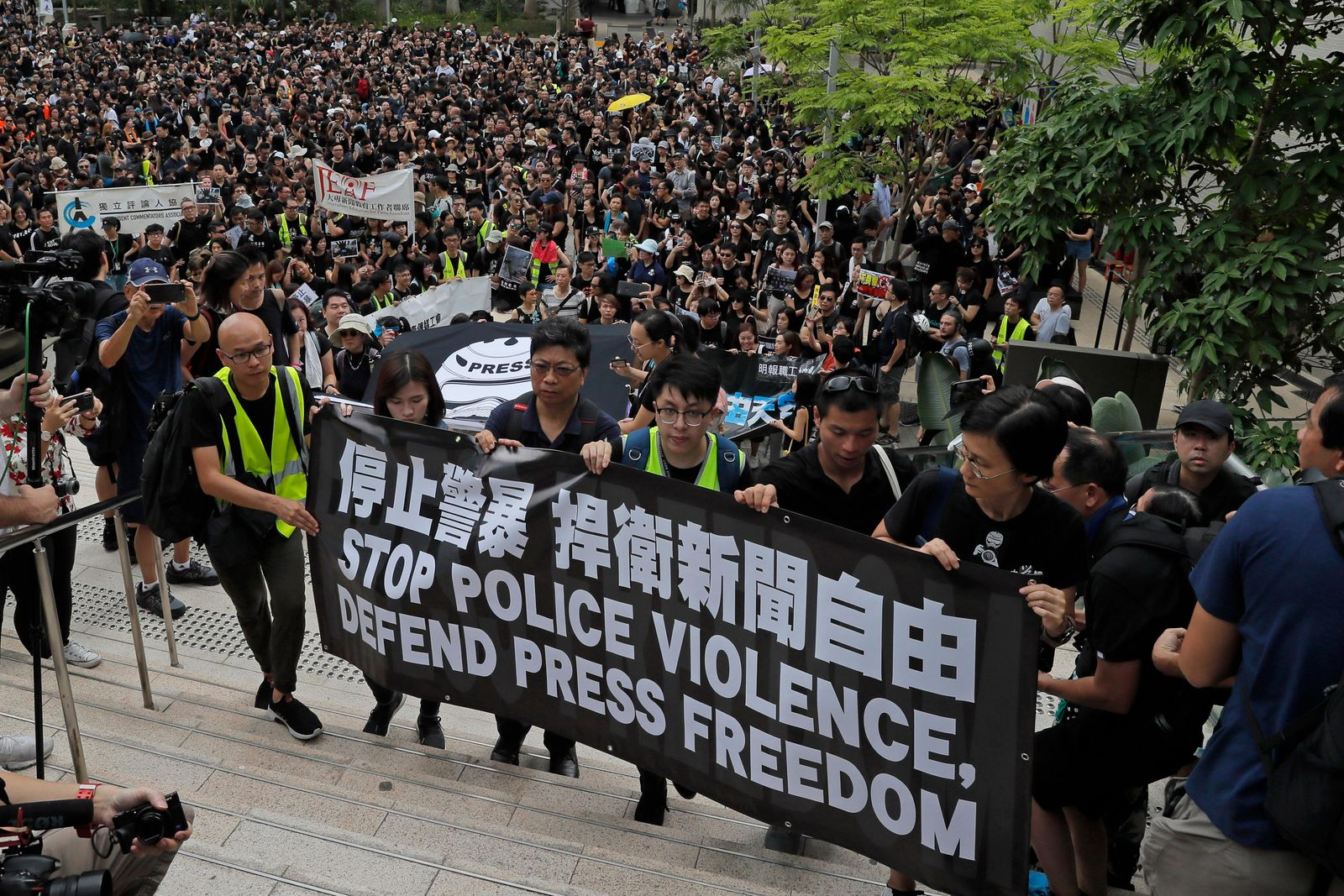 "Hundreds of journalists hold banner with words ""Stop police violence, defend press freedom"" during a silent march to police headquarters and the government headquarters in Hong Kong, Sunday, July 14, 2019. They demand police to stop assaulting journalists and obstructing reporting. (AP Photo/Kin Cheung)"