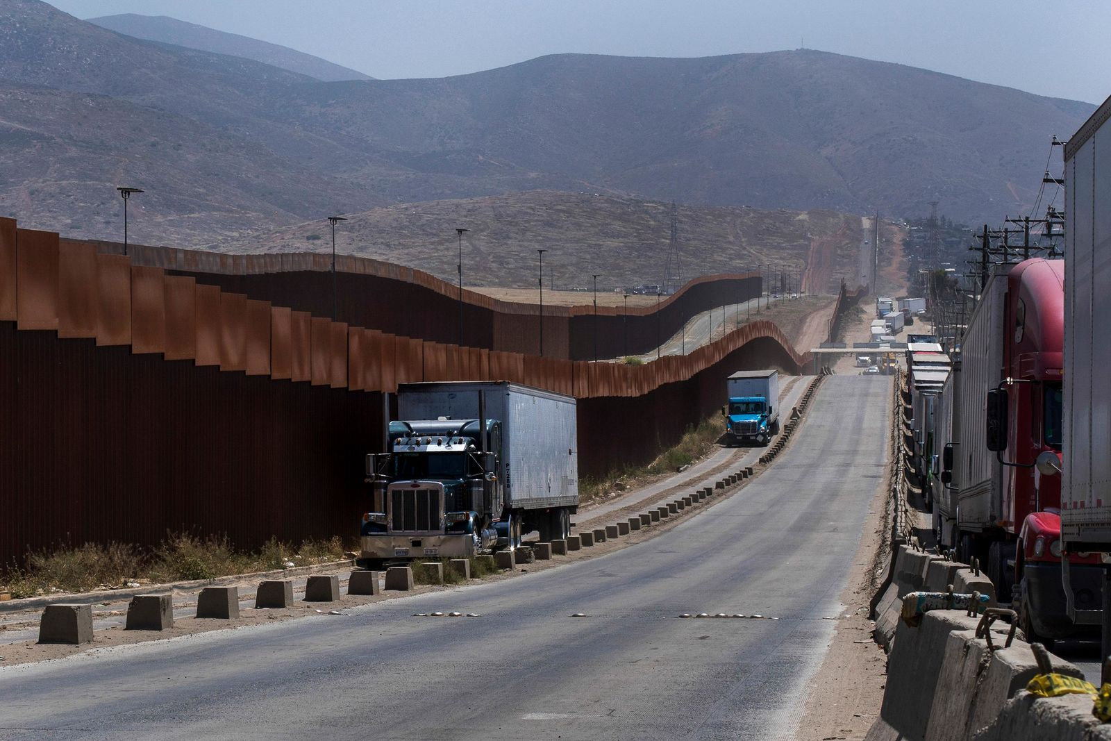 Trucks pass along a border wall as they get into position to cross into the United States at the border in Tijuana, Mexico, Friday, June 7, 2019.{ } (AP Photo/Hans-Maximo Musielik)