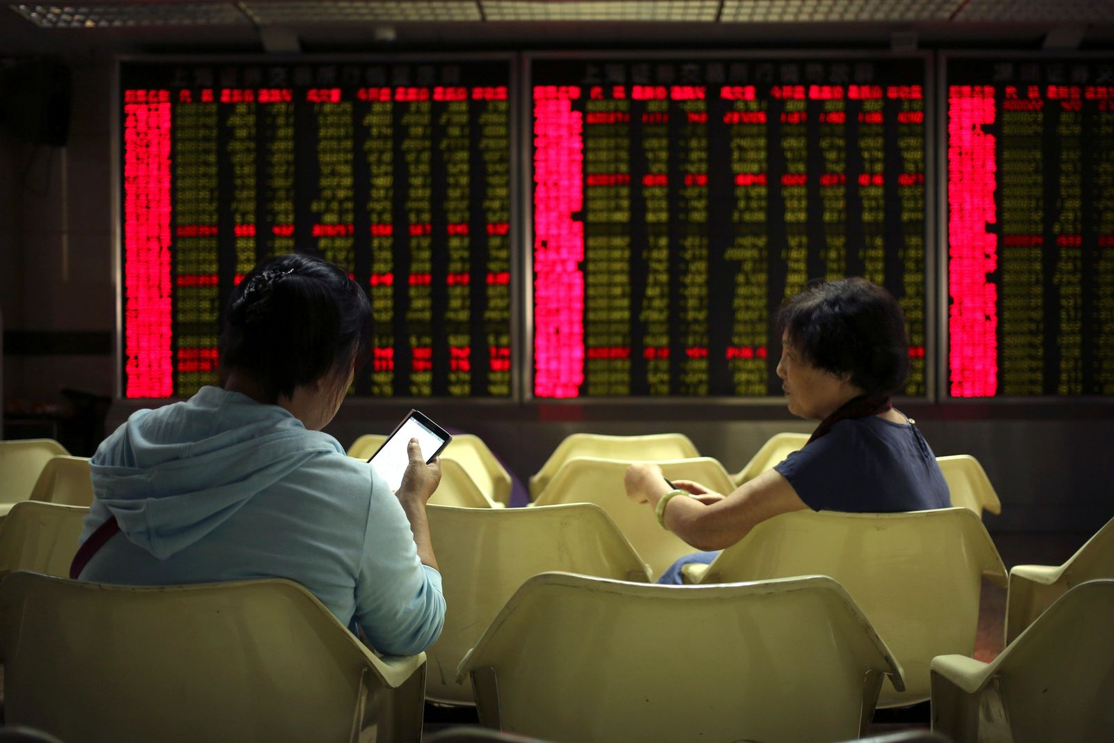 Chinese investors monitor stock prices at a brokerage house in Beijing, Friday, Aug. 2, 2019. . (AP Photo/Mark Schiefelbein)